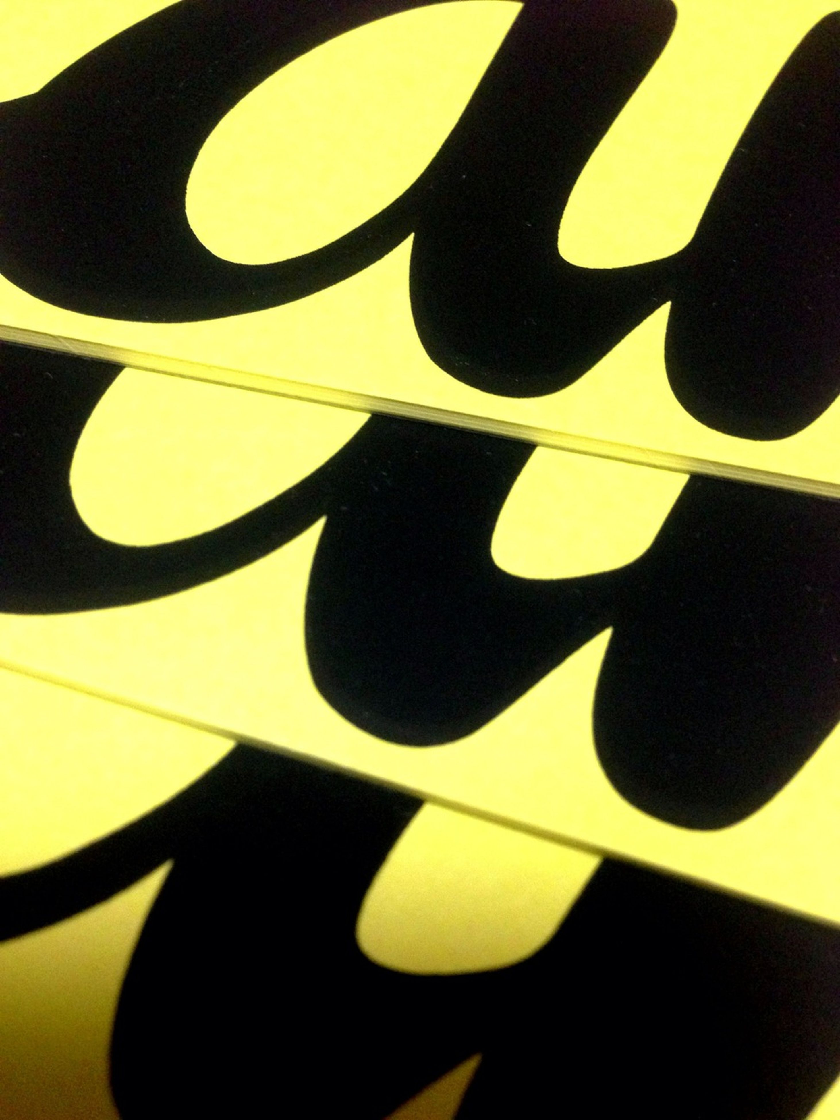 indoors, creativity, art and craft, art, yellow, close-up, design, still life, pattern, shape, wall - building feature, shadow, no people, decoration, black color, craft, hanging, detail, sunlight, human representation