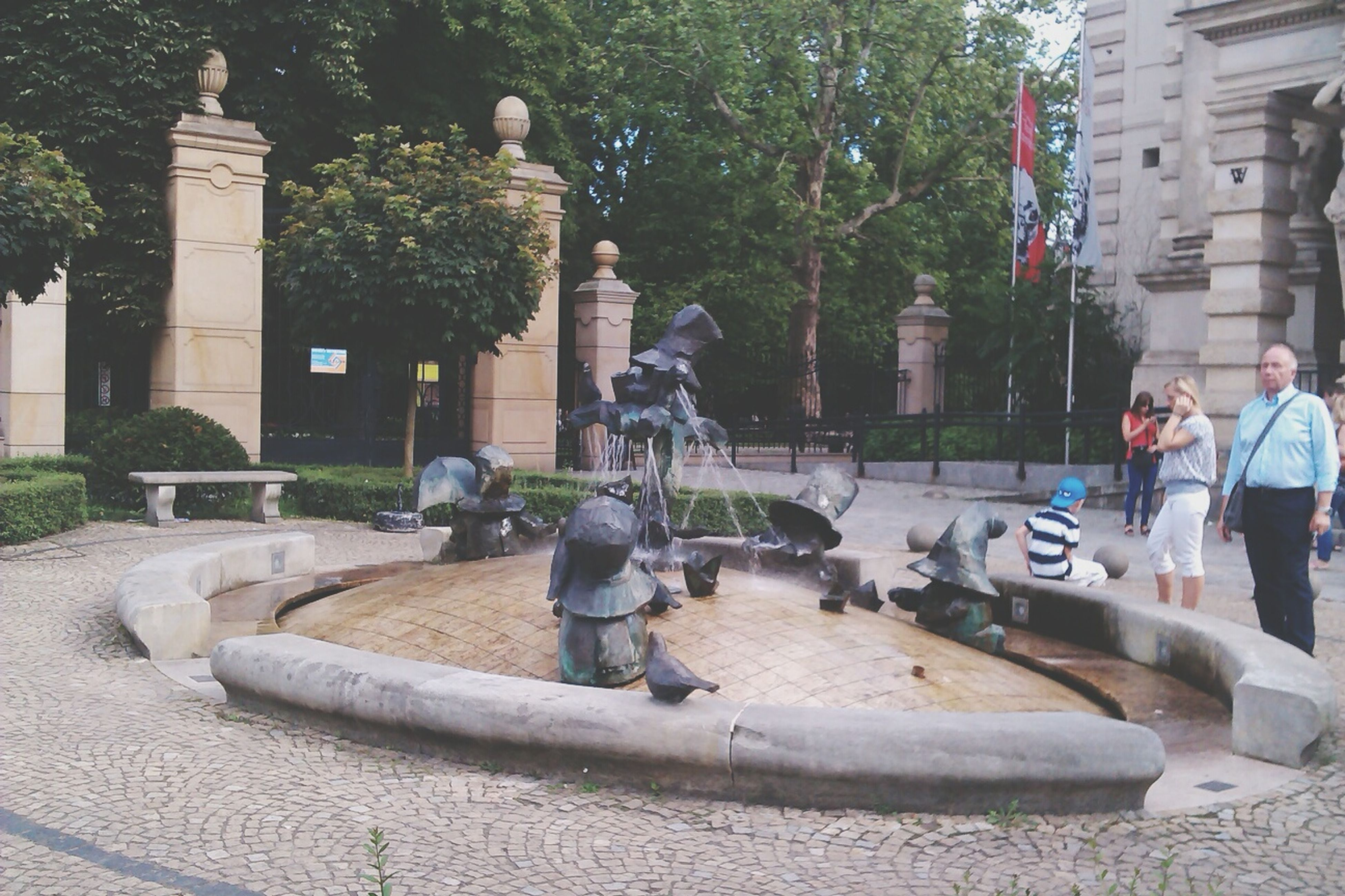 tree, building exterior, built structure, statue, architecture, sculpture, fountain, water, park - man made space, sitting, incidental people, city, art and craft, leisure activity, men, day, human representation, lifestyles