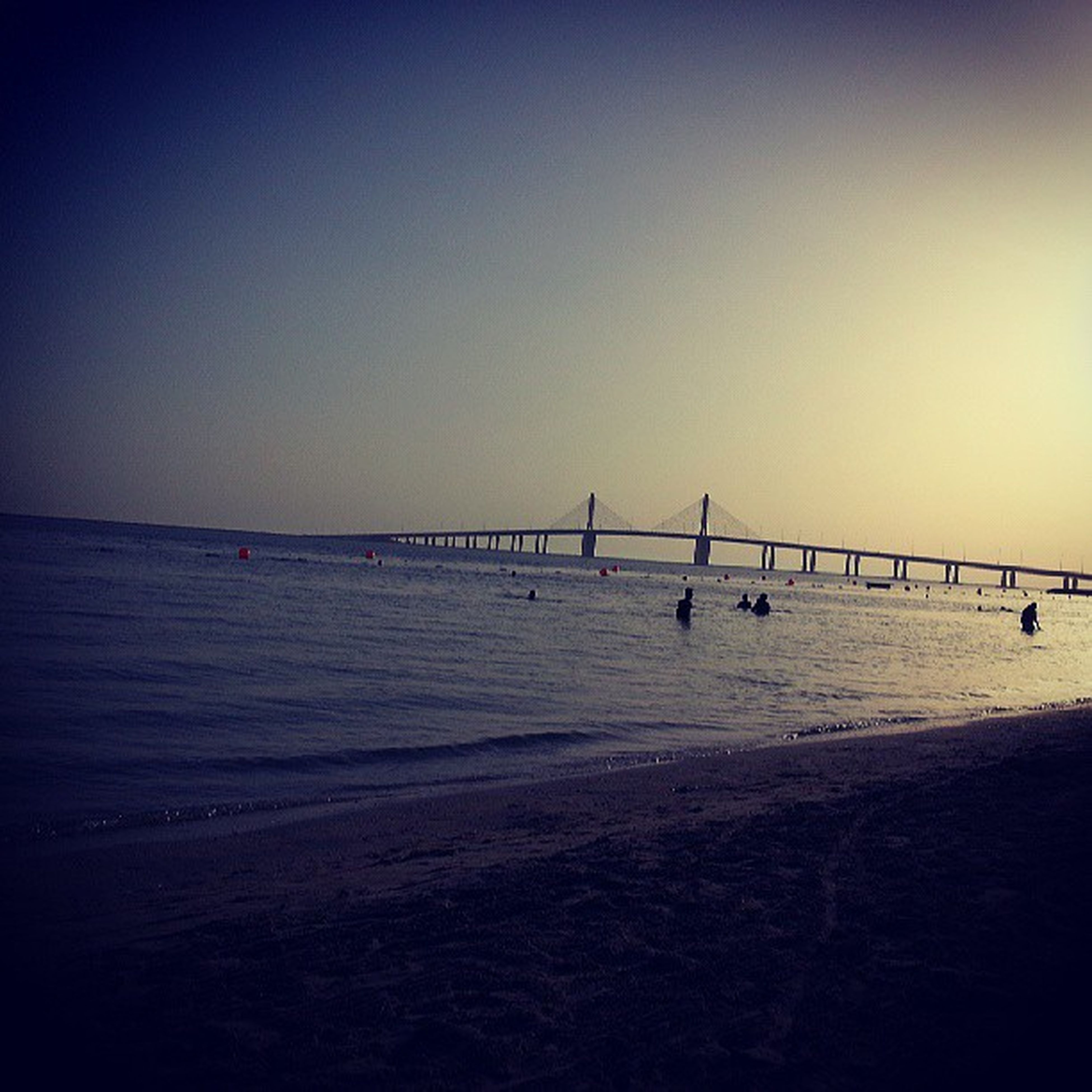 sea, water, clear sky, copy space, beach, horizon over water, tranquil scene, tranquility, scenics, sunset, nature, beauty in nature, silhouette, shore, incidental people, outdoors, idyllic, sand, sky, built structure
