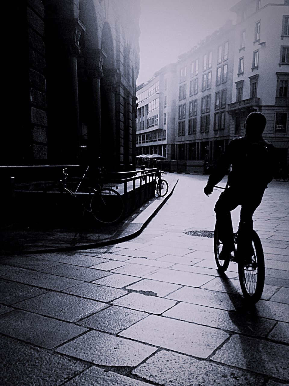 Rear View Of Silhouette Person Cycling On Road
