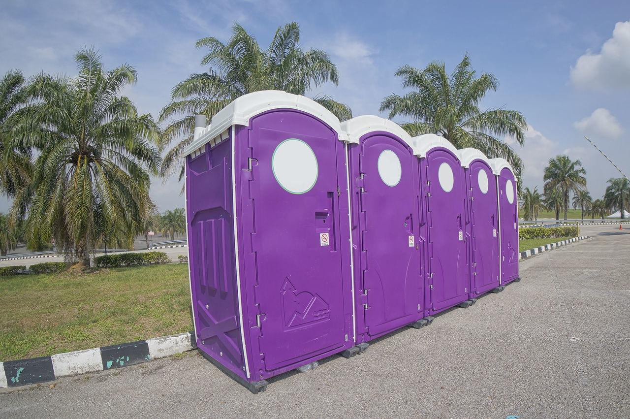a row of portable toilets public convenience Clouds Convenience Grass Portable Toilets Purple Sky Tarmac