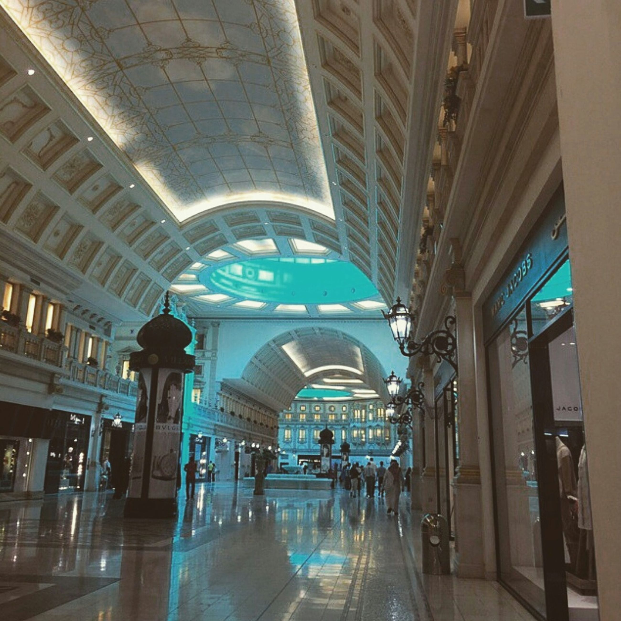 indoors, ceiling, architecture, built structure, illuminated, men, lifestyles, walking, person, large group of people, modern, railroad station, incidental people, travel, subway station, shopping mall, leisure activity, city life, flooring