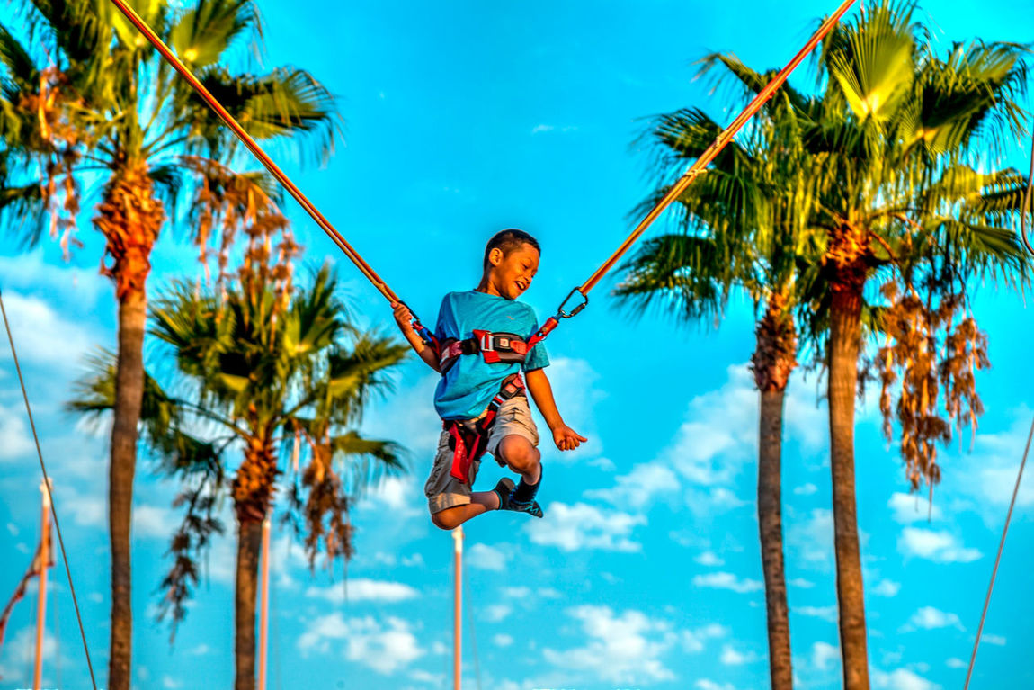 Young boy enjoying the catapult swing Adrenaline Adrenaline Junkie Blue Boy Casual Clothing Catapult Cloud Cloud - Sky Day Enjoyment Fun Growth Leisure Activity Lifestyles Low Angle View Nature Outdoors Play Portrait Sky Swing Tranquility Tree