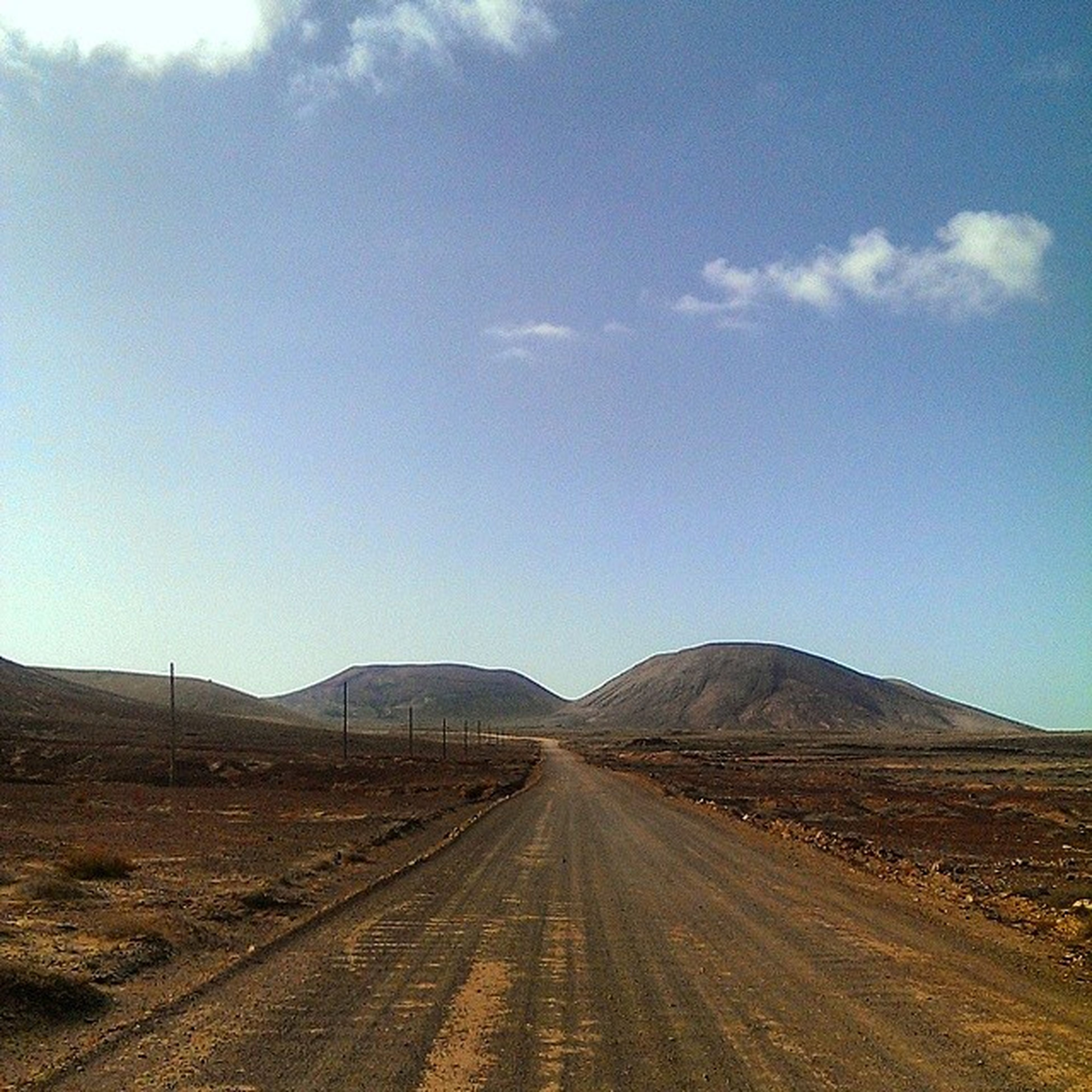 the way forward, diminishing perspective, road, vanishing point, landscape, transportation, sky, tranquil scene, mountain, tranquility, blue, country road, desert, dirt road, nature, scenics, non-urban scene, mountain range, empty, remote