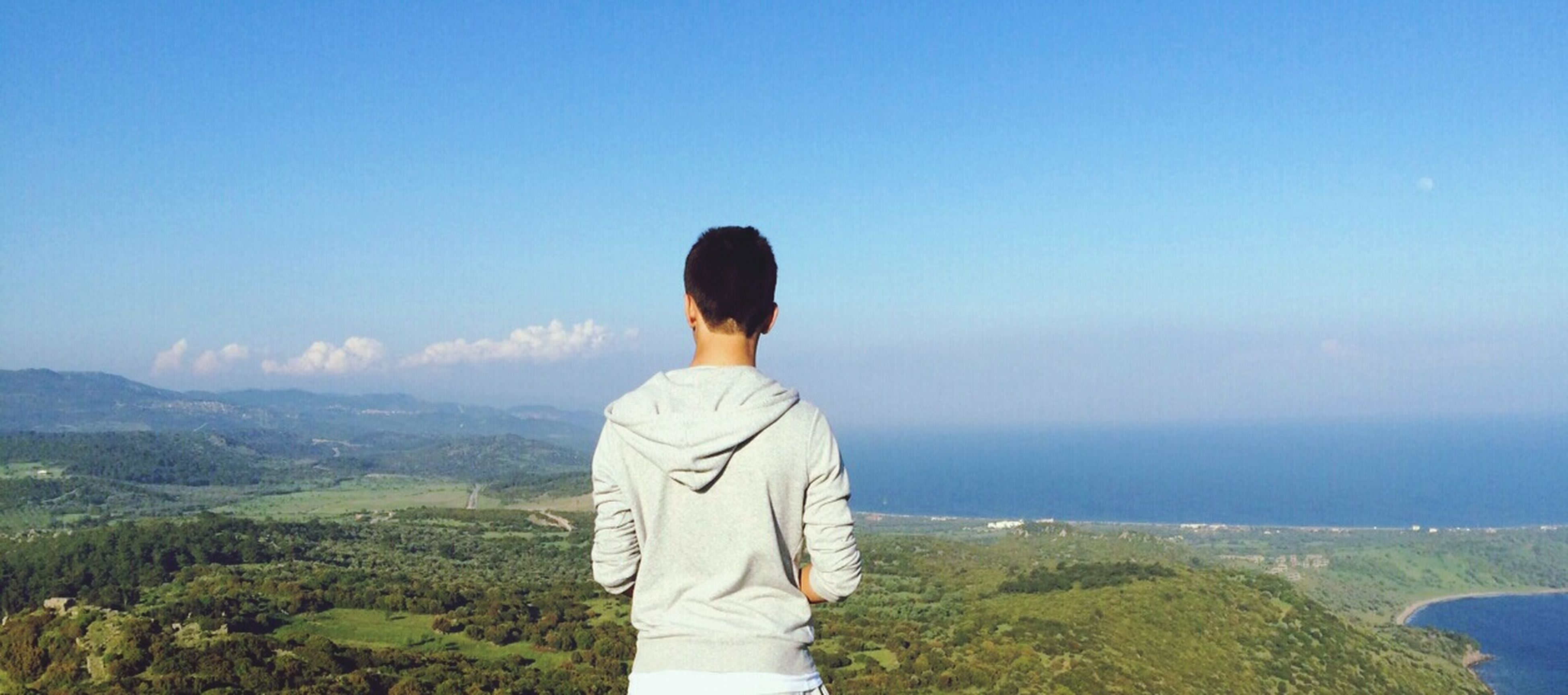 standing, rear view, tranquil scene, tranquility, lifestyles, scenics, beauty in nature, sky, leisure activity, three quarter length, nature, blue, casual clothing, waist up, mountain, getting away from it all, looking at view, landscape