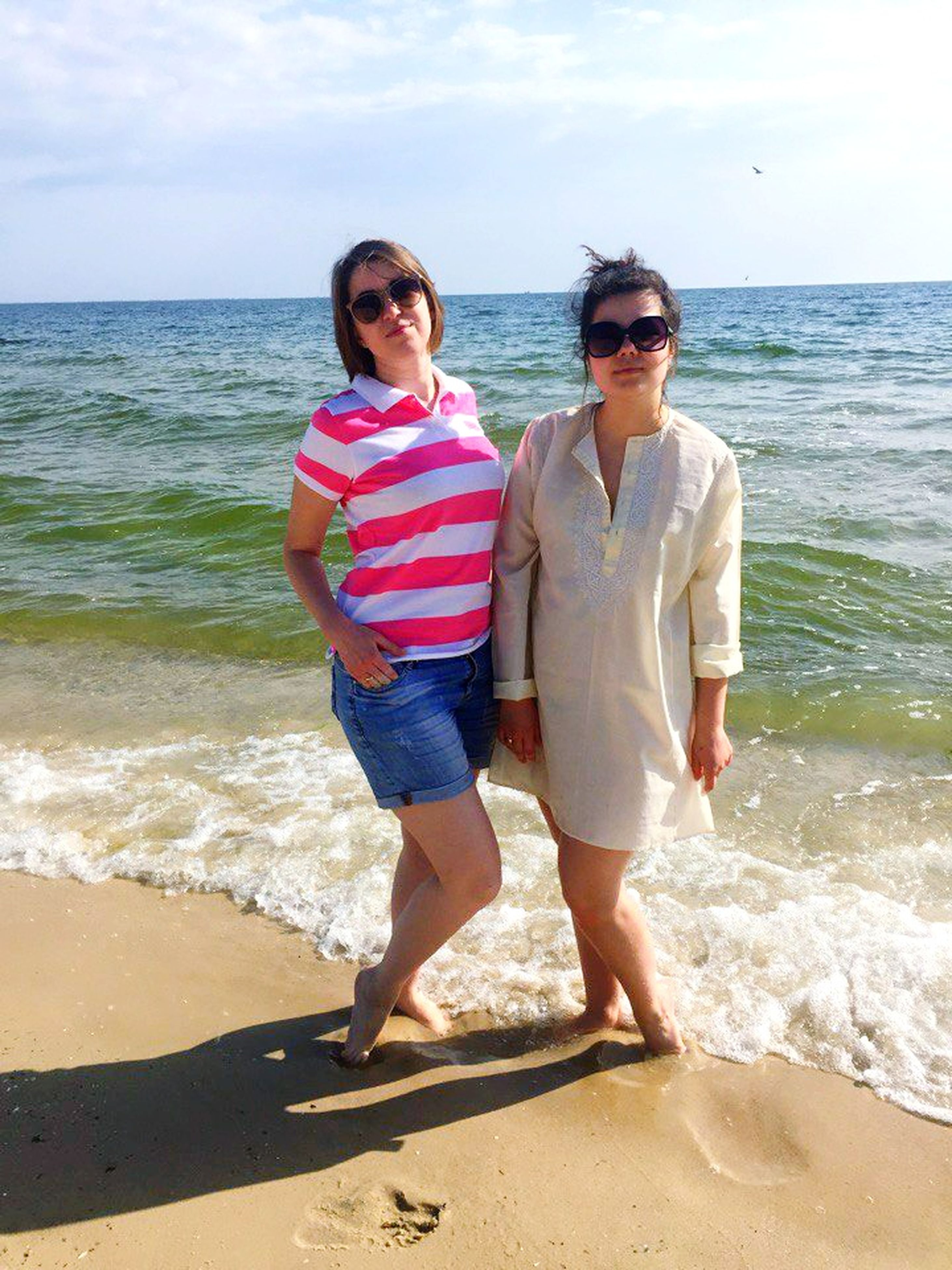 sea, two people, beach, sunglasses, horizon over water, young women, young men, young adult, leisure activity, full length, sand, real people, water, togetherness, sky, day, casual clothing, front view, nature, vacations, outdoors, standing, lifestyles, happiness, scenics, smiling, beauty in nature