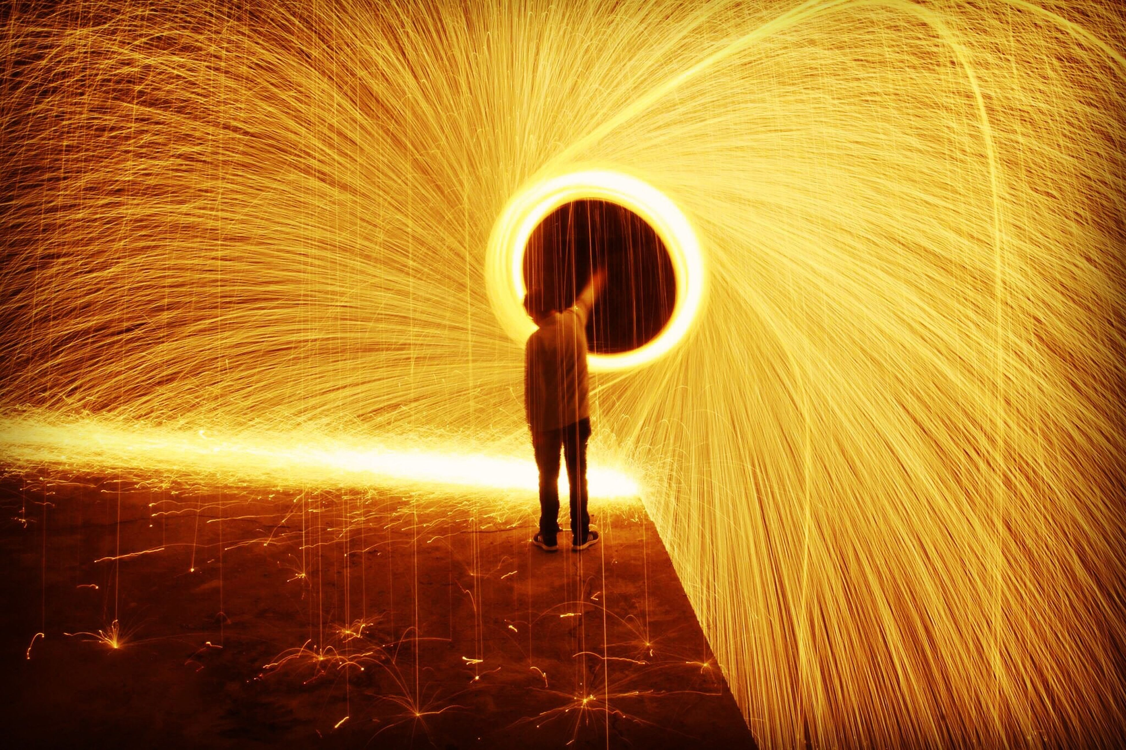 motion, long exposure, wire wool, one person, night, full length, spinning, illuminated, circle, glowing, blurred motion, standing, tunnel, skill, one woman only, activity, burning, performance, one young woman only, adult, real people, adults only, women, lifestyles, indoors, young adult, people, young women, bedroom