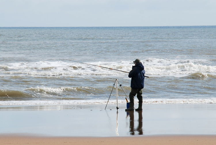 Beach Beauty In Nature Clear Sky Day Fishing From Beach Full Length Horizon Over Water Leisure Activity Men Nature One Person Outdoors People Real People Sand Scenics Sea Sea And Sky Sea Fishing From Beach Sky Standing Water Wave