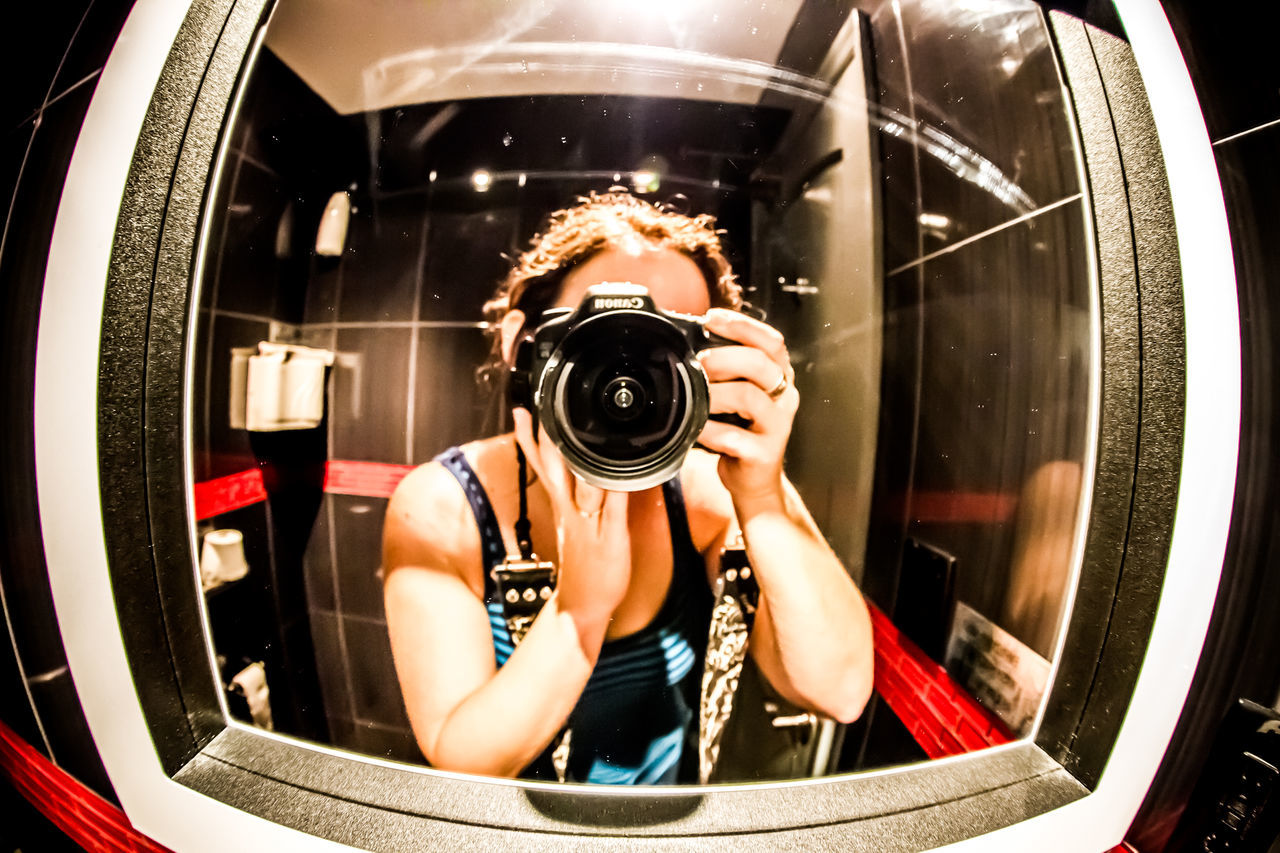 photography themes, camera - photographic equipment, photographing, technology, real people, digital camera, photographer, leisure activity, one person, professional occupation, camera, slr camera, holding, lifestyles, indoors, modern, digital single-lens reflex camera, close-up, day, people