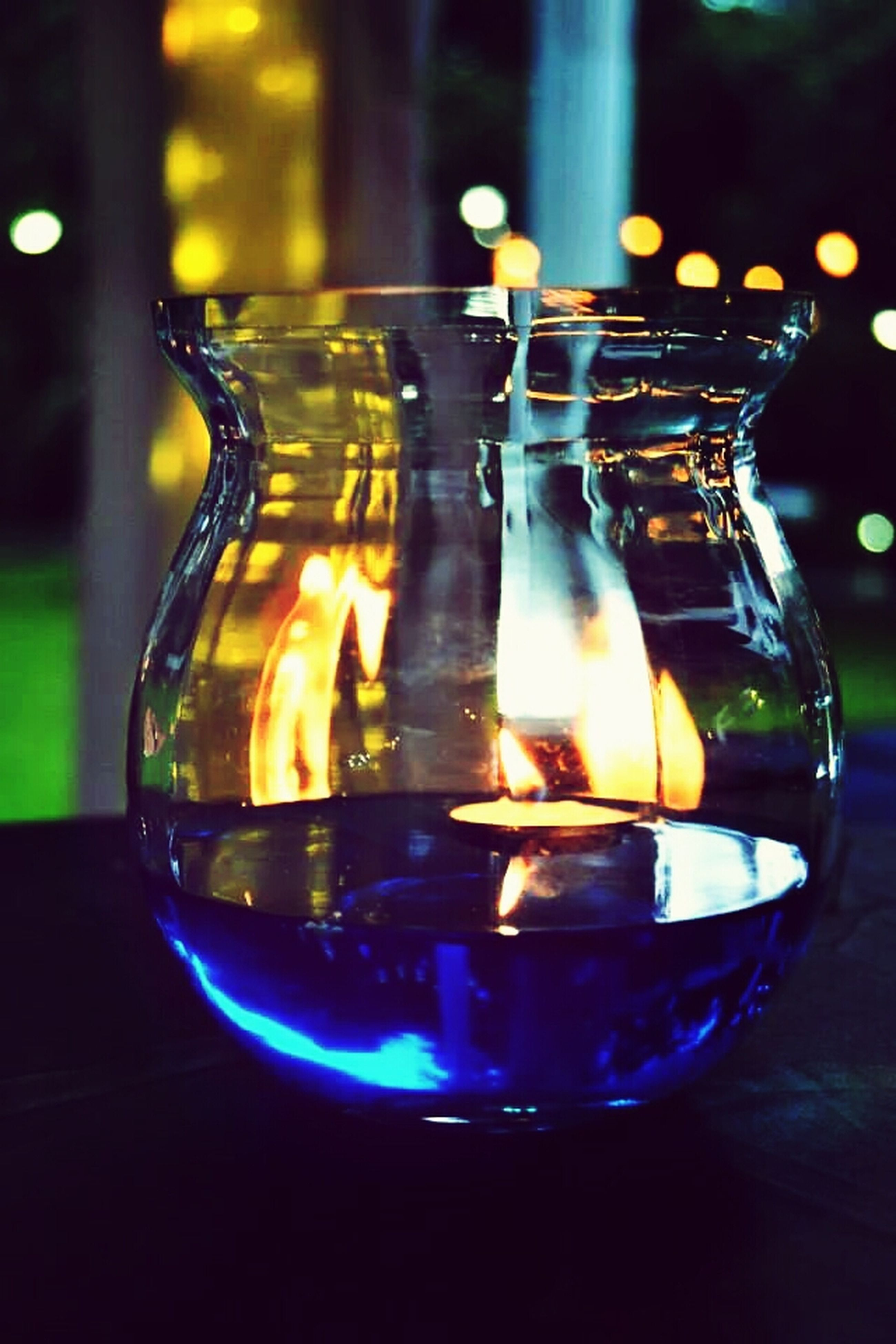 illuminated, indoors, glowing, glass - material, close-up, lighting equipment, burning, night, candle, focus on foreground, light - natural phenomenon, flame, reflection, transparent, yellow, no people, decoration, table, motion, still life