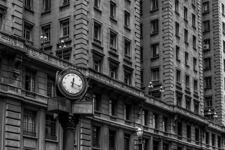 Black and white iconic old style street clock in front of buildings with windows with old street lamp posts in downtown area of São Paulo, Brazil, one of the biggest cities in the world. Architecture BIG Black And White Building Business City Clock Downtown Facade Building Hour Hurry Iconic Late Metropolis Minute Old Pace Schedule Second Stress Time Timing Town Urban Window