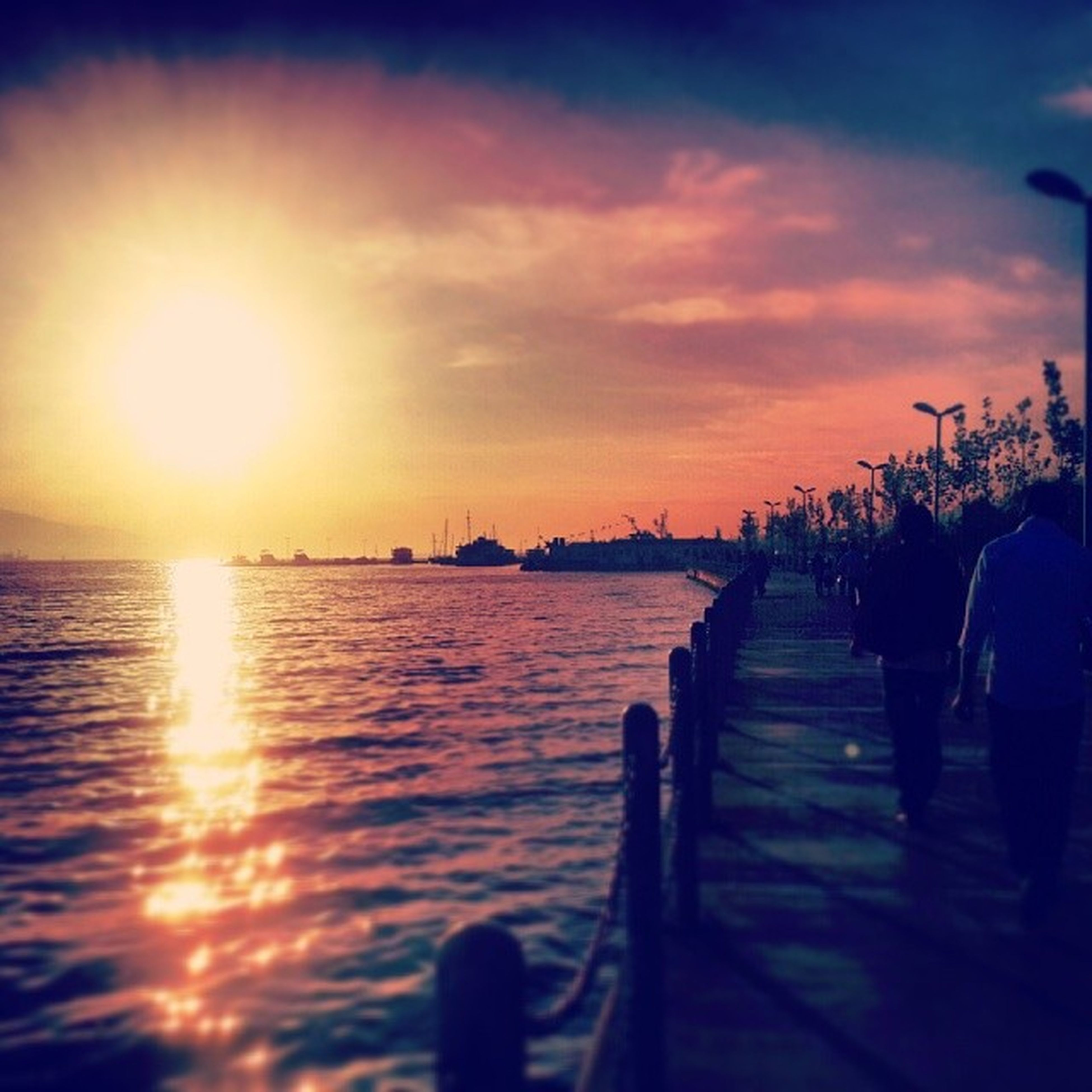 sunset, water, sun, sea, silhouette, sky, sunlight, sunbeam, reflection, pier, scenics, tranquil scene, lens flare, railing, tranquility, nature, beauty in nature, orange color, horizon over water, idyllic