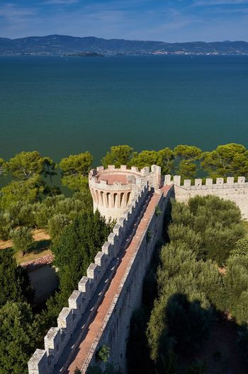 Fortress of the Lion, and Lake Trasimeno, Castiglione del Lago, Umbria Brick Wall History Castle Fort Fortress Fortress Wall Blue Sky Hills Lake Lake View Nature Outdoors No People Lago Trasimeno Umbria Italy Castiglione Del Lago Architecture Horizon Over Water Water Built Structure Architectural Lines Historic Medieval Architecture