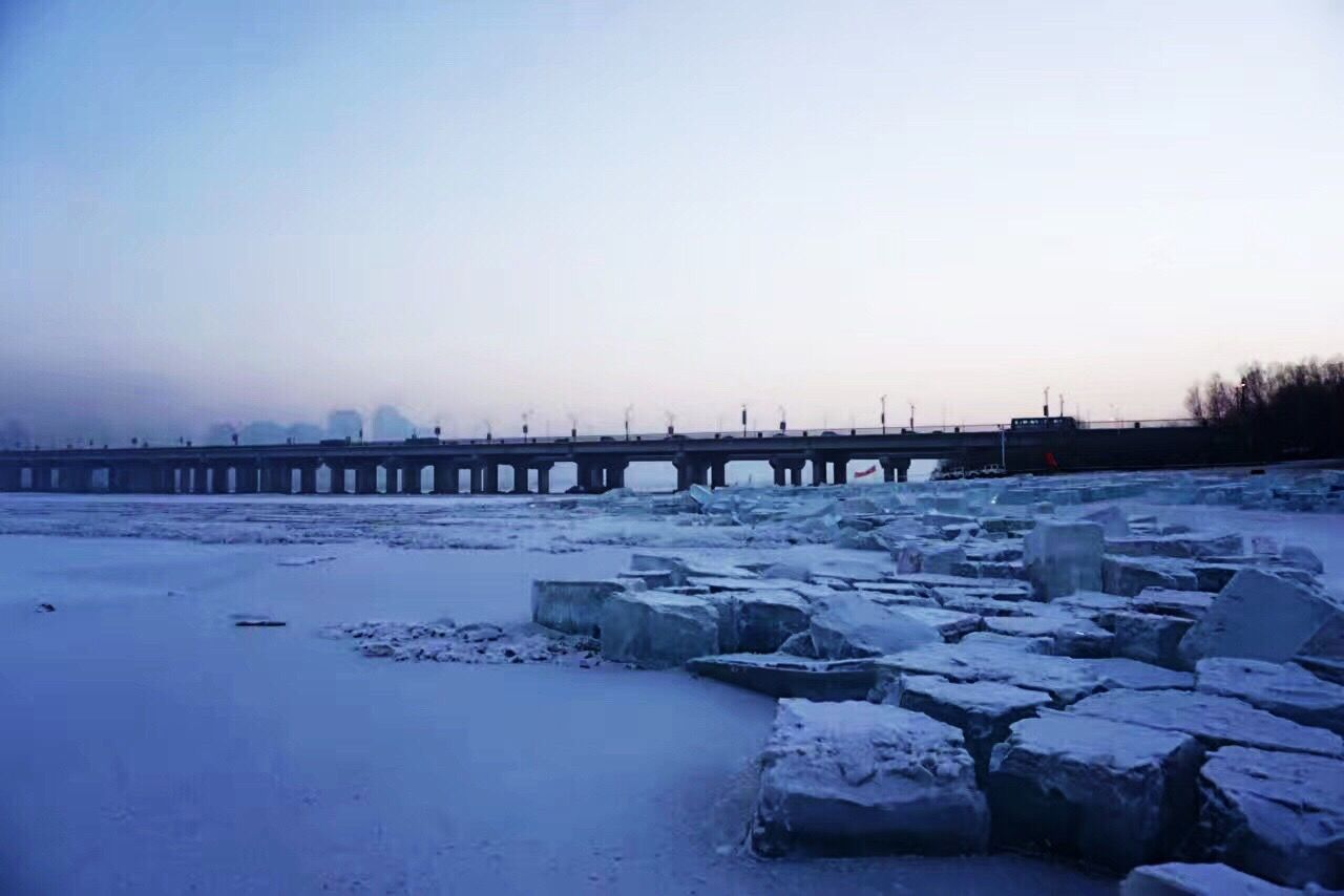 winter, cold temperature, snow, bridge - man made structure, built structure, ice, water, sunset, frozen, outdoors, river, architecture, connection, sky, nature, no people, travel destinations, city, building exterior, beauty in nature, scenics, clear sky, day