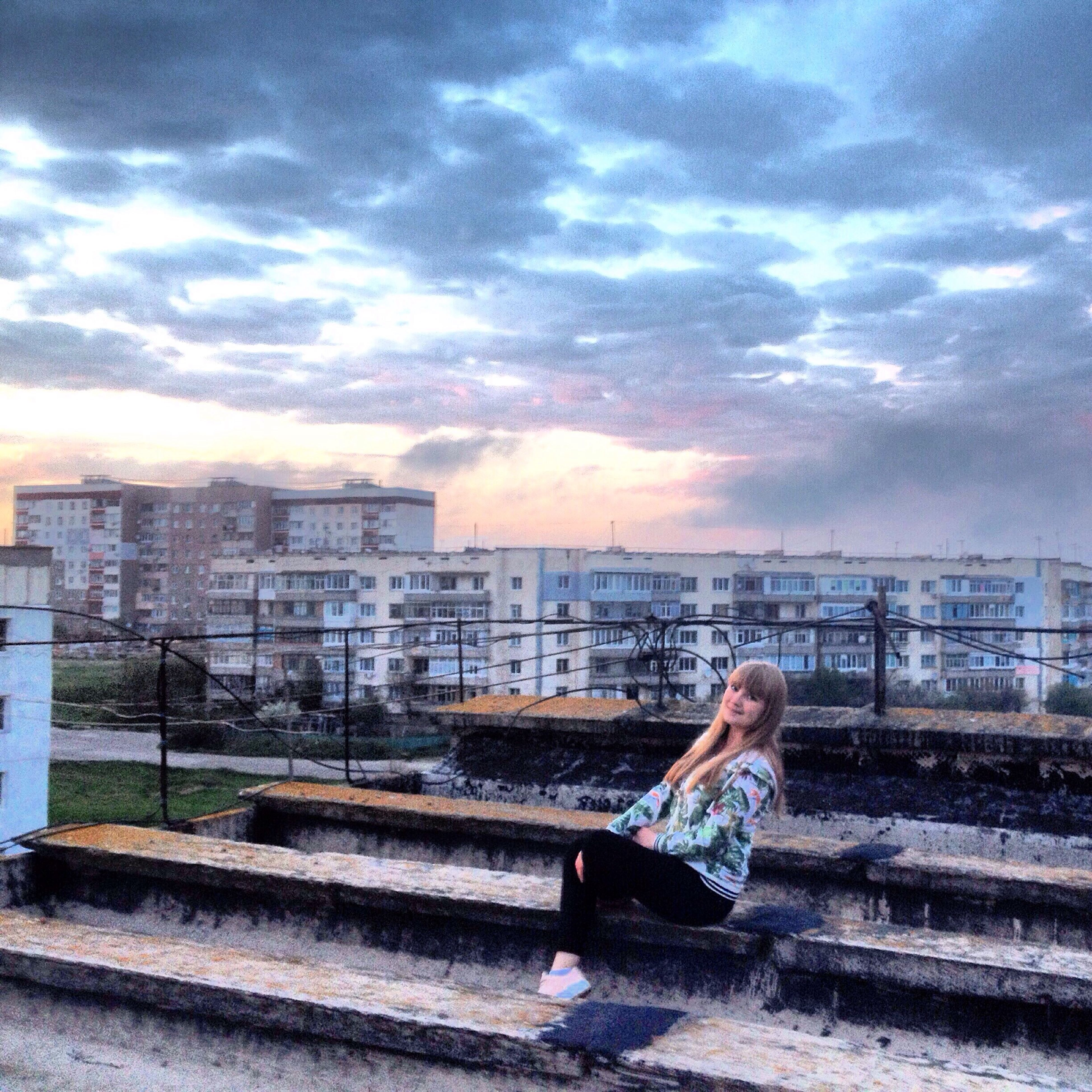 sky, one animal, building exterior, animal themes, built structure, cloud - sky, architecture, bird, cloud, one person, sunset, cloudy, animals in the wild, side view, outdoors, railing, full length, sitting, perching, wood - material