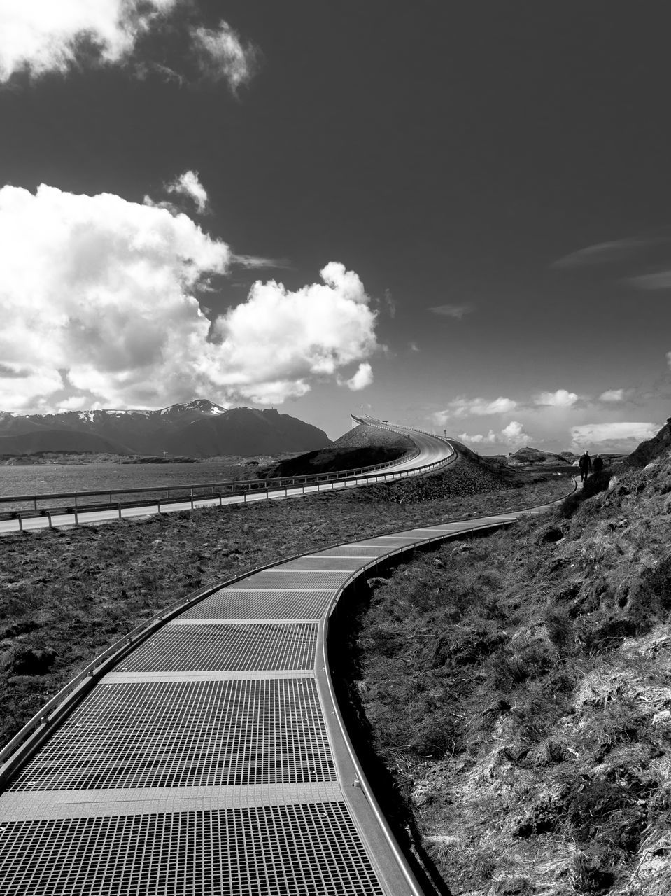 Walkway Against Cloudy Sky On Sunny Day