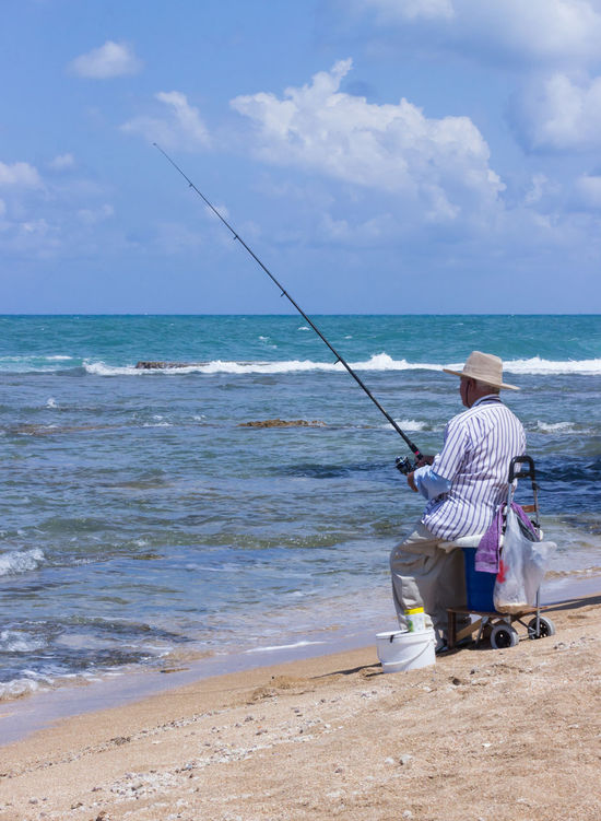Acre, Israel - May 28, 2016: Elderly man fishing with a fishing rod on the beach in Akre, Israel Acre Activities Adults Age Beach Day Elderly Fish Fisherman Fishing Grandfather Happiness Hobby Israel Lifestyles Man Nature Outdoors Person Rod Sea Sea And Sky Seniors Sky Water