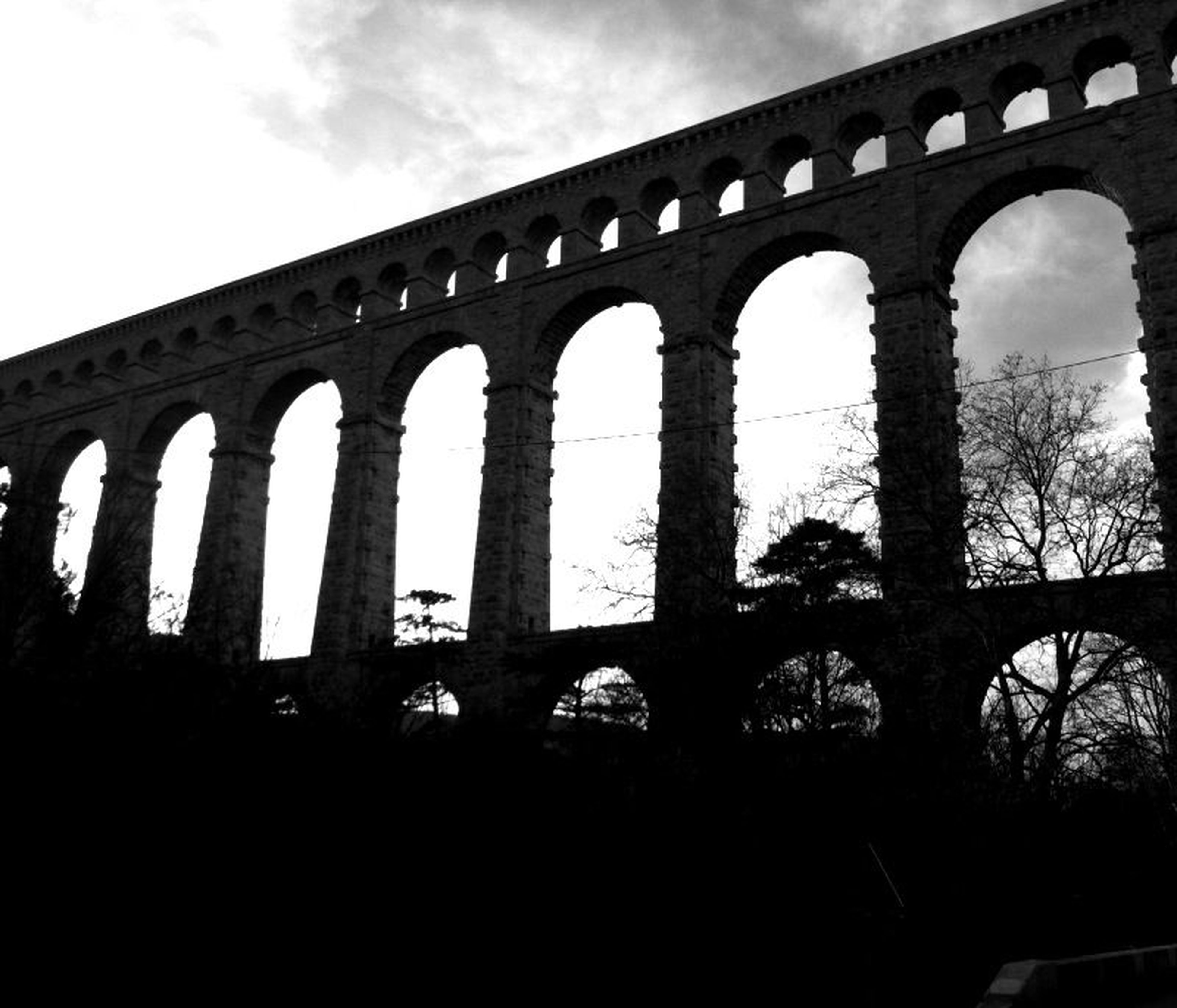 architecture, built structure, arch, low angle view, sky, history, building exterior, silhouette, arch bridge, arched, bridge - man made structure, architectural column, travel destinations, famous place, the past, connection, outdoors, no people, day, old