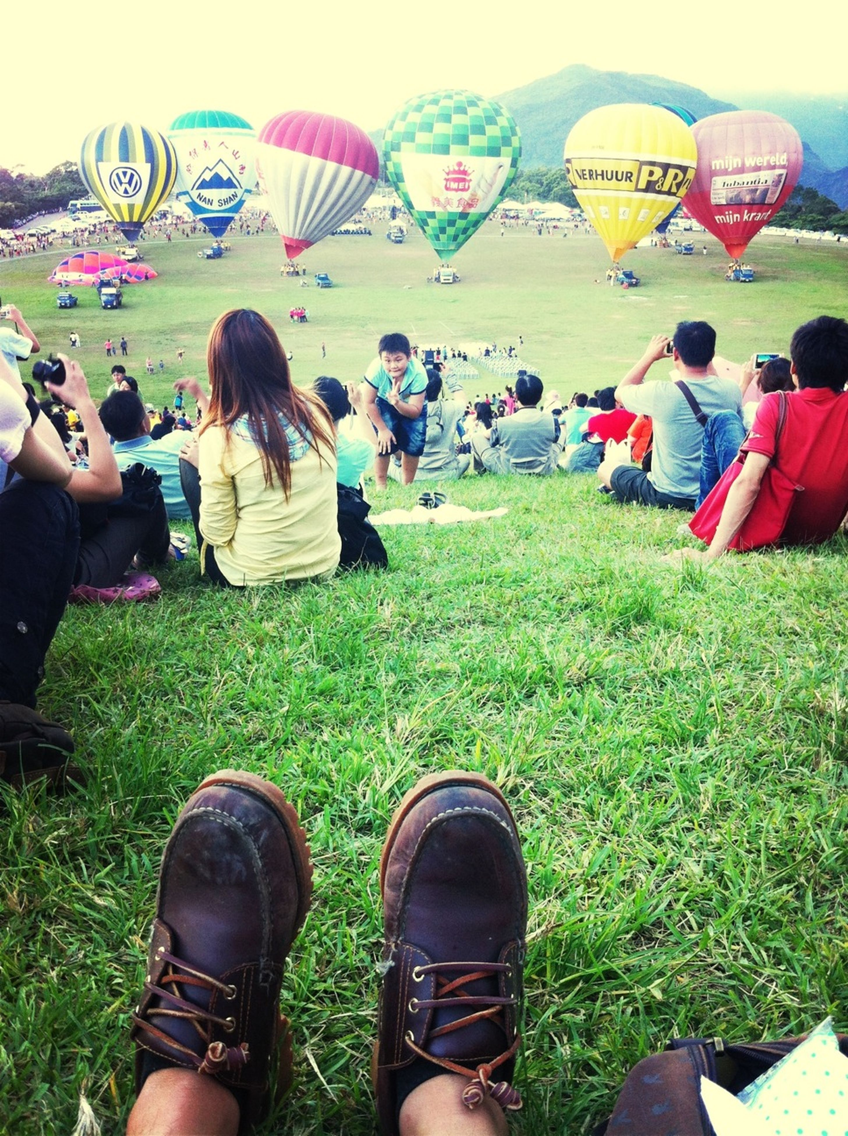 grass, lifestyles, leisure activity, low section, men, large group of people, person, field, shoe, relaxation, sitting, togetherness, grassy, standing, friendship, casual clothing, personal perspective
