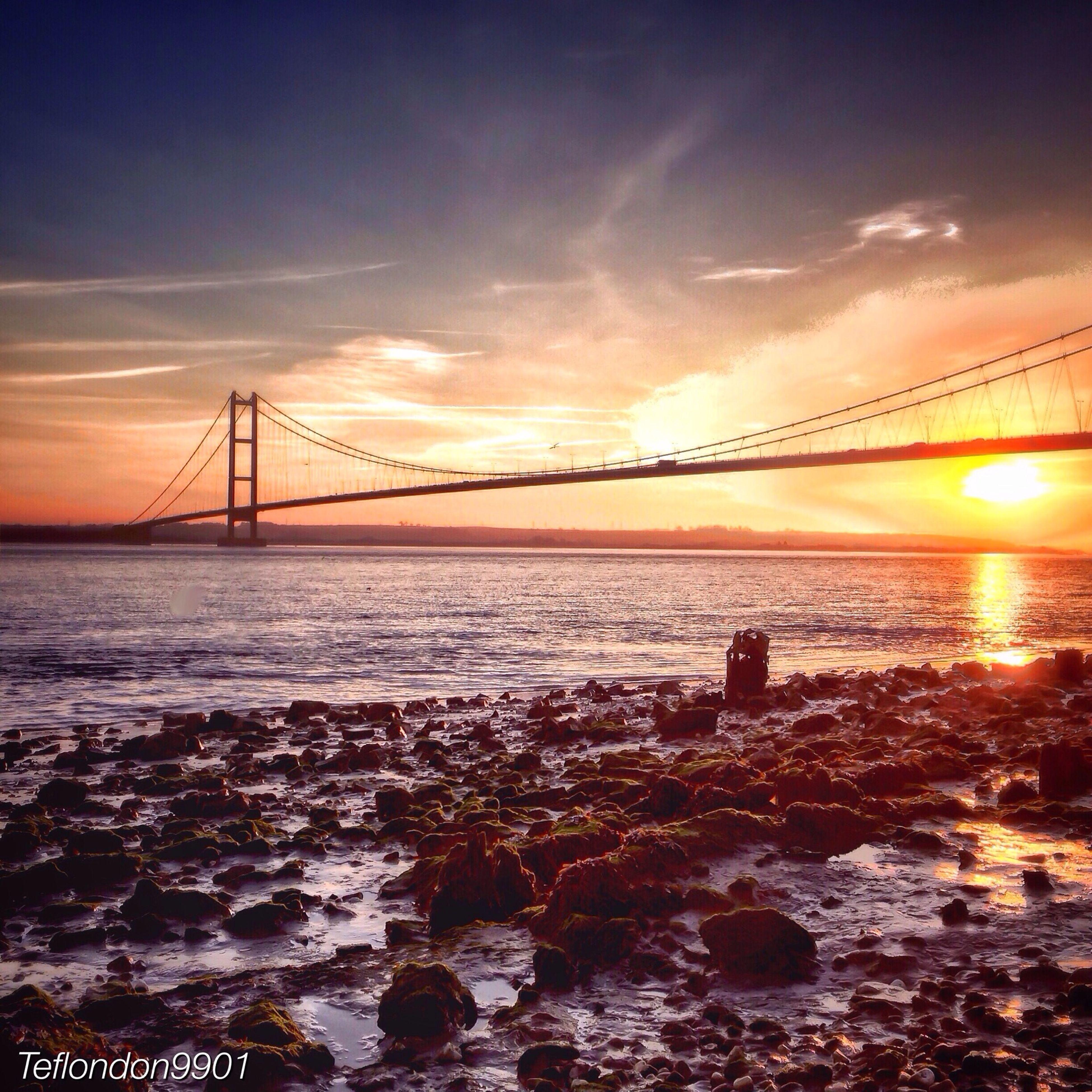 sunset, connection, water, bridge - man made structure, sun, sky, suspension bridge, orange color, scenics, engineering, sea, beauty in nature, silhouette, built structure, tranquil scene, tranquility, bridge, nature, river, sunbeam