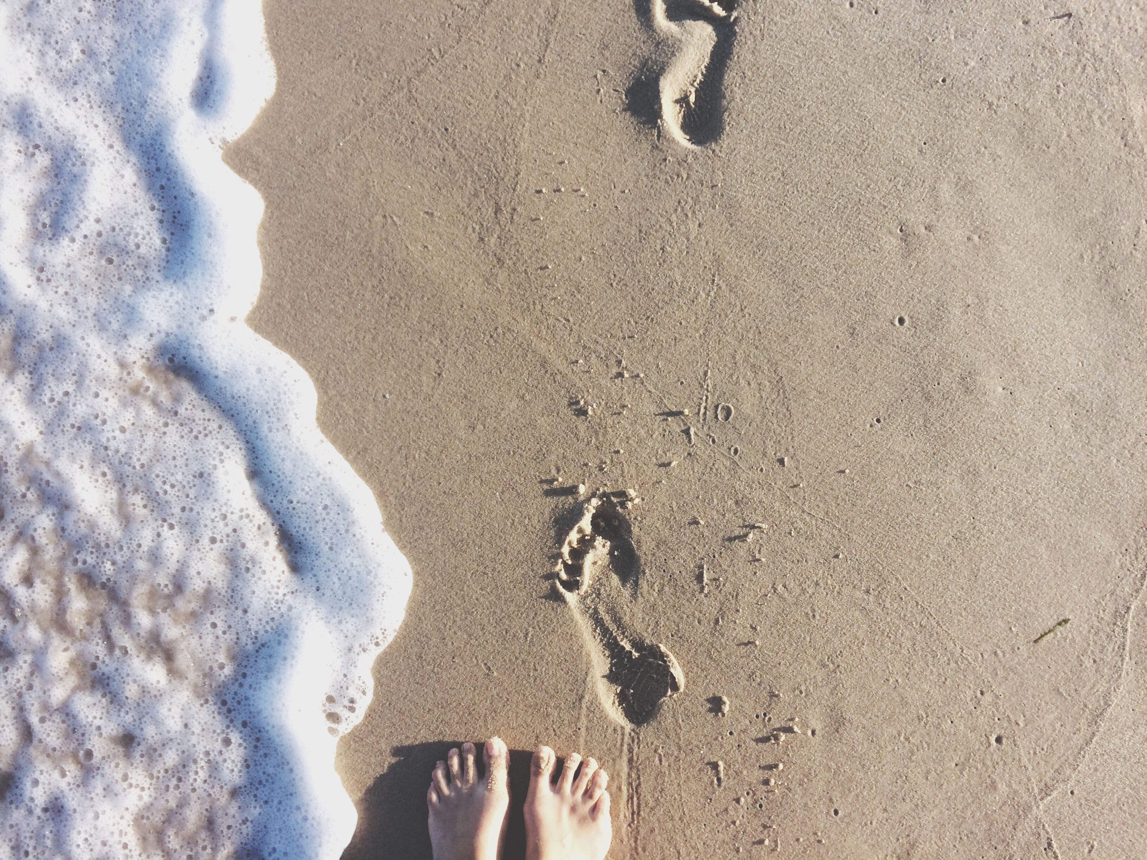 low section, person, personal perspective, beach, standing, human foot, sand, lifestyles, high angle view, leisure activity, shoe, unrecognizable person, shore, barefoot, footprint, water, outdoors