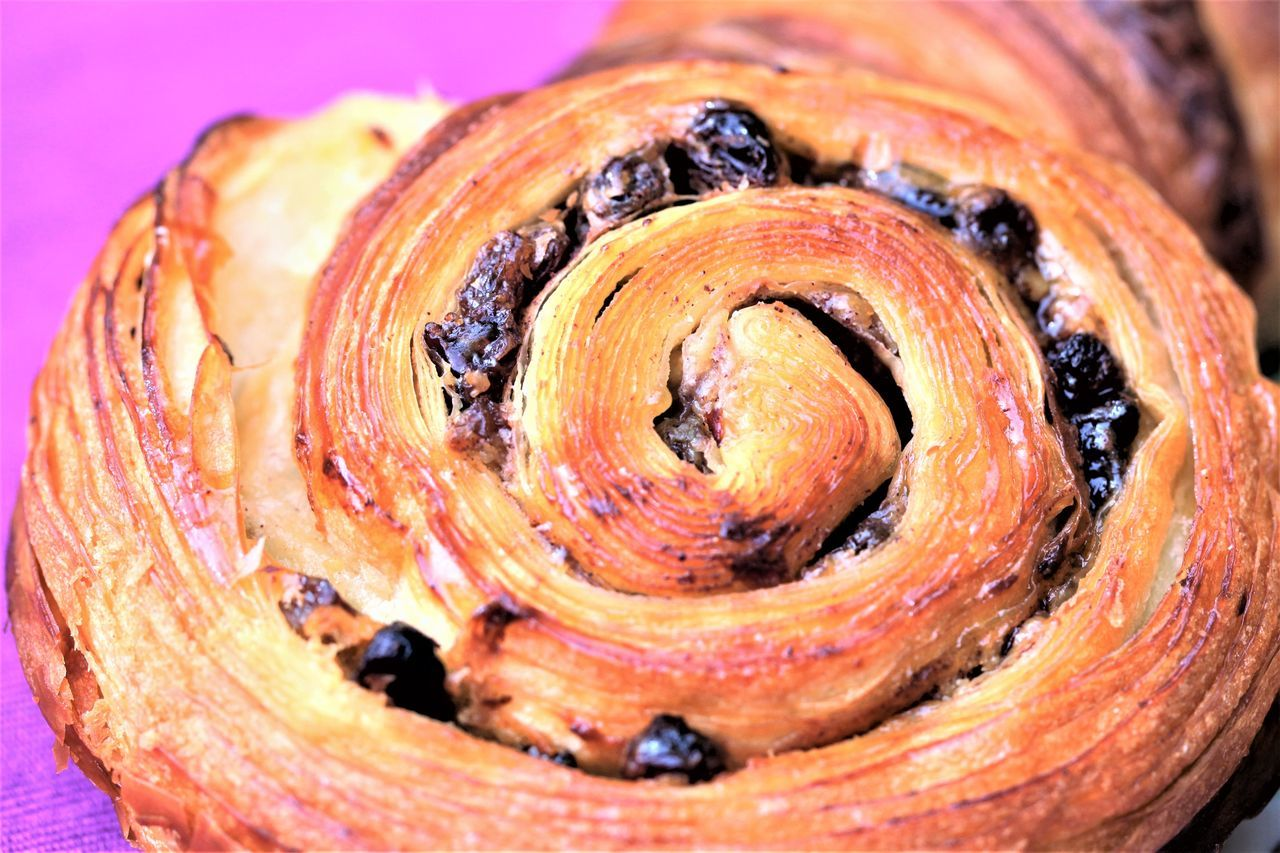 Cinnamon & Raisin Scroll with flaky layers of pastry against purple background Baked Goods Bakery Cinnamon Close-up Delicious Escargot Flaky Pastry Food No People Pastry Purple Raisins Scroll Sweet Food