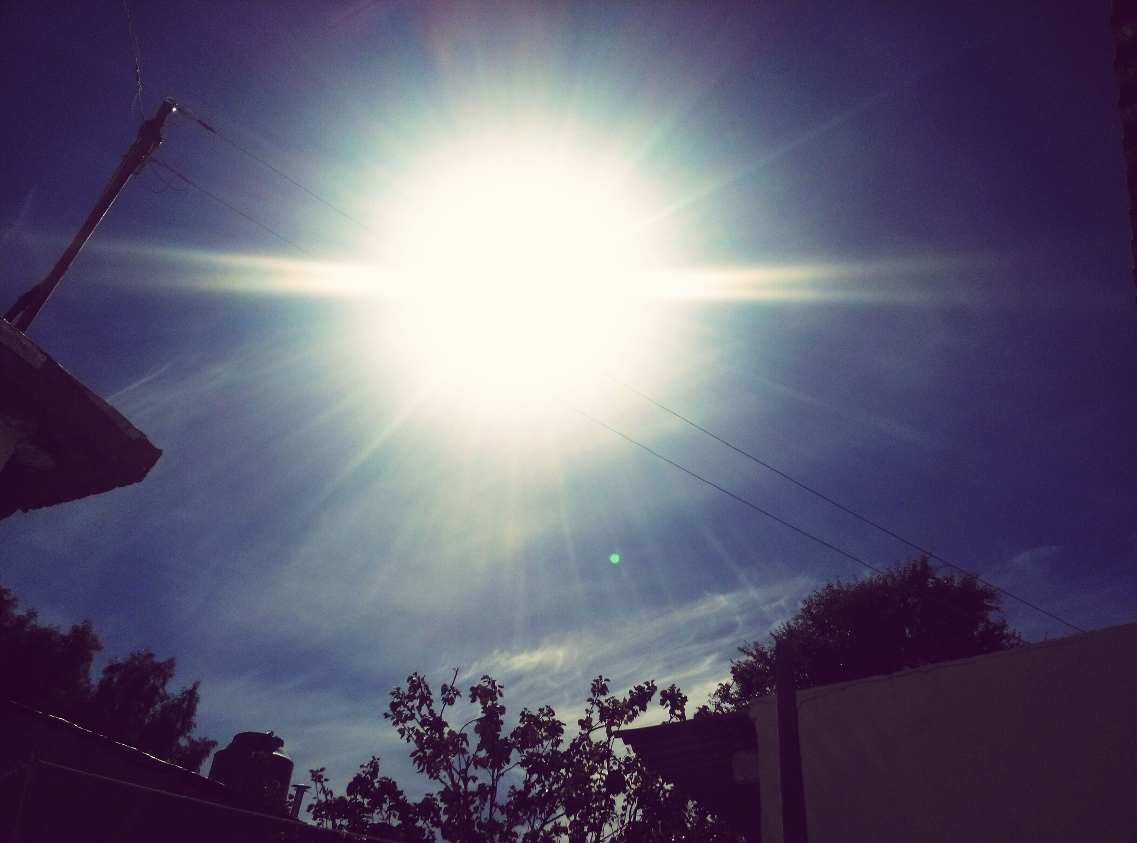 sun, low angle view, sunbeam, sunlight, lens flare, sky, silhouette, tree, built structure, bright, sunny, blue, nature, building exterior, beauty in nature, architecture, power line, day, outdoors, house