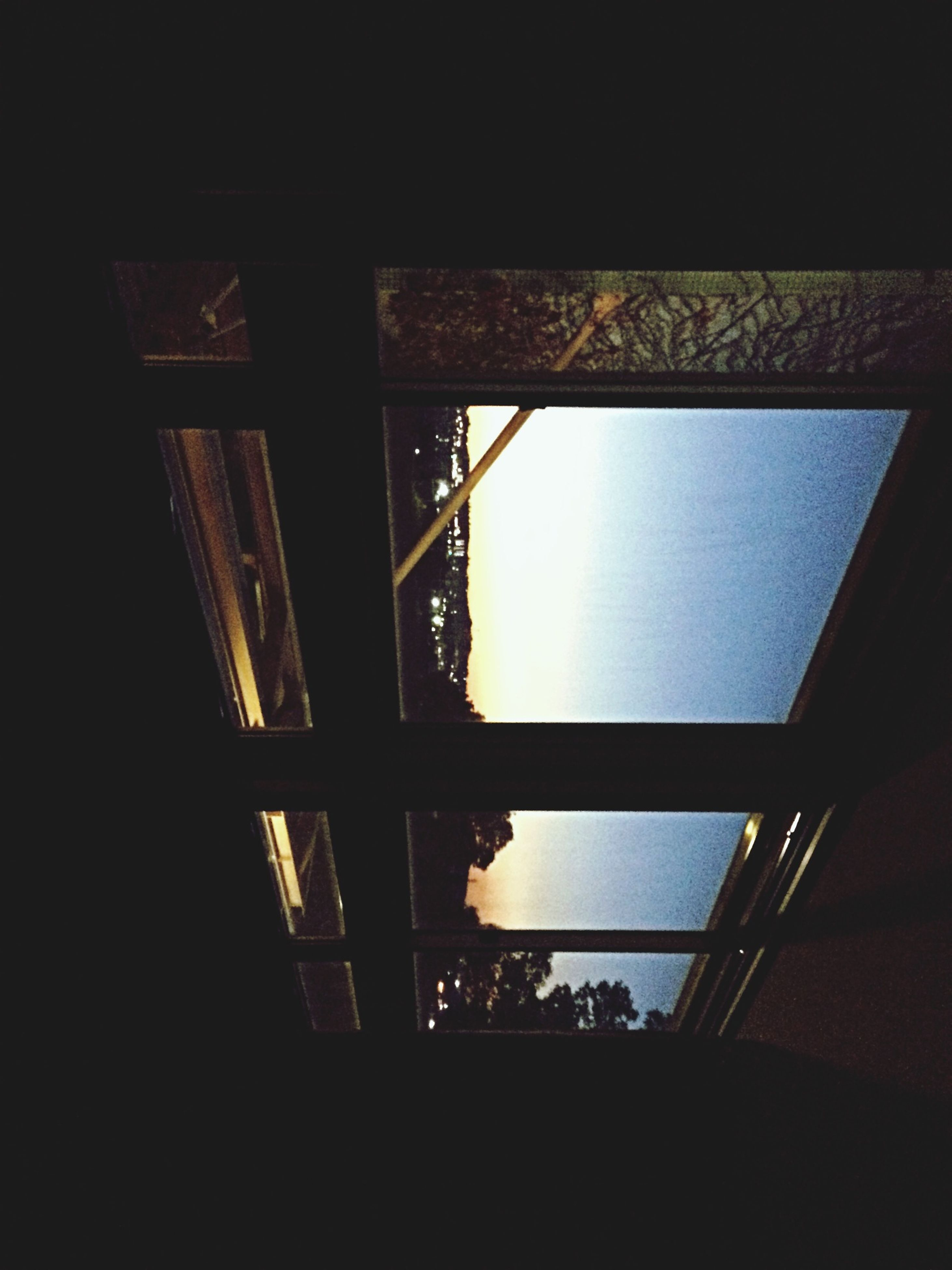 indoors, window, low angle view, built structure, glass - material, architecture, home interior, silhouette, transparent, dark, house, ceiling, sunlight, no people, day, copy space, sky, window sill, clear sky, wall