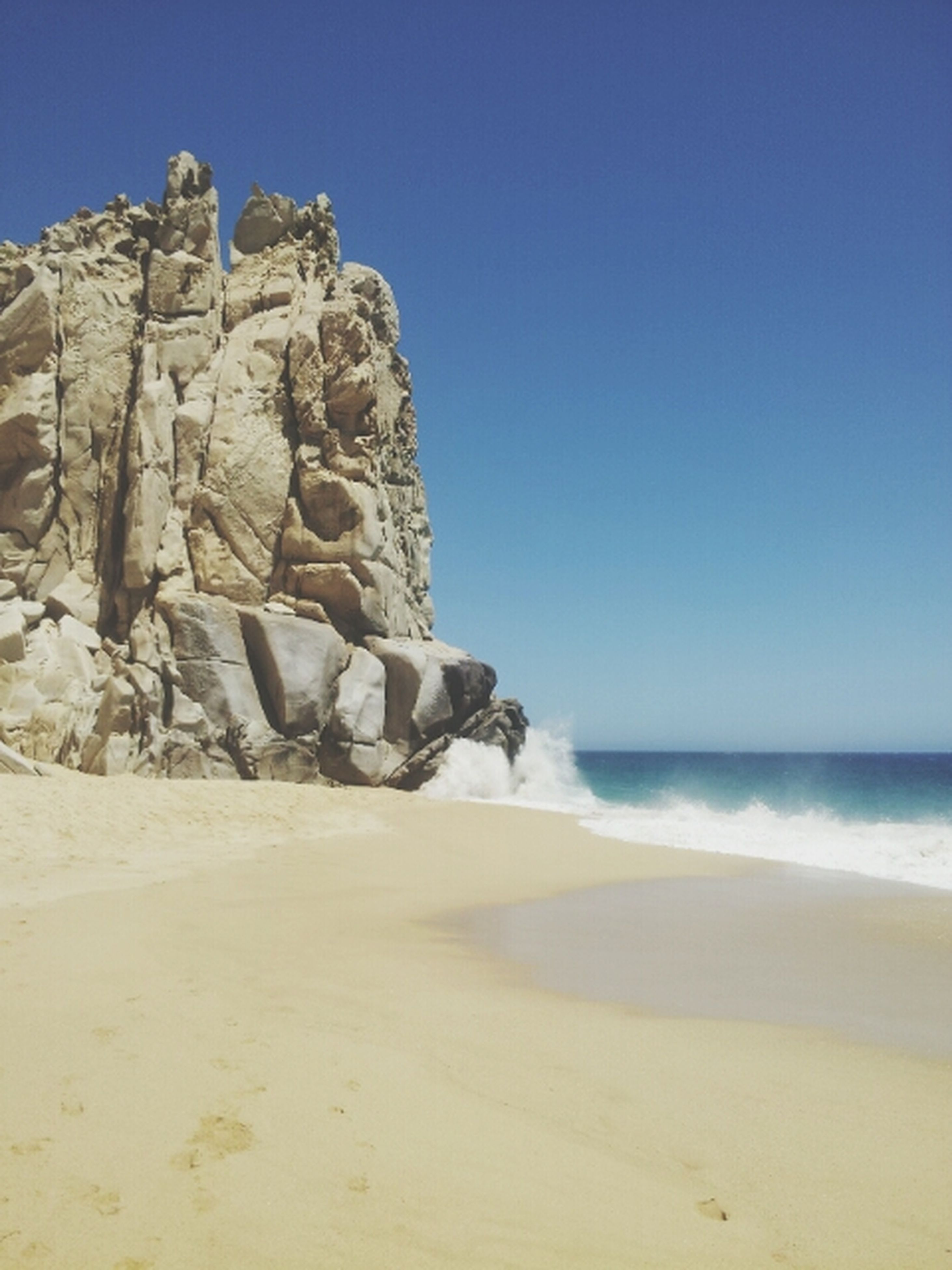 sea, beach, sand, clear sky, horizon over water, shore, water, tranquility, tranquil scene, blue, copy space, scenics, nature, beauty in nature, rock formation, sunlight, rock - object, coastline, day, sky