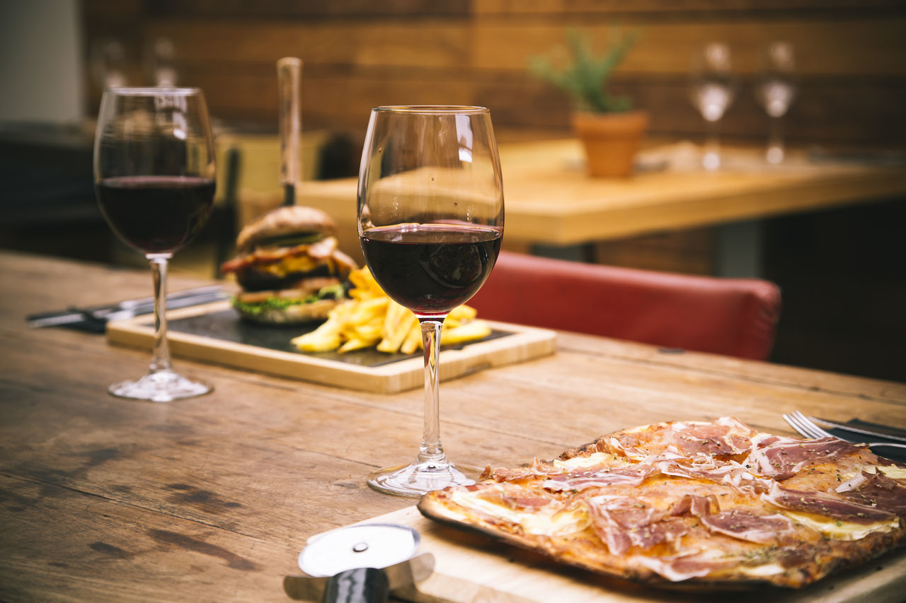 Red Wine With Pizza Served On Wooden Table At Restaurant