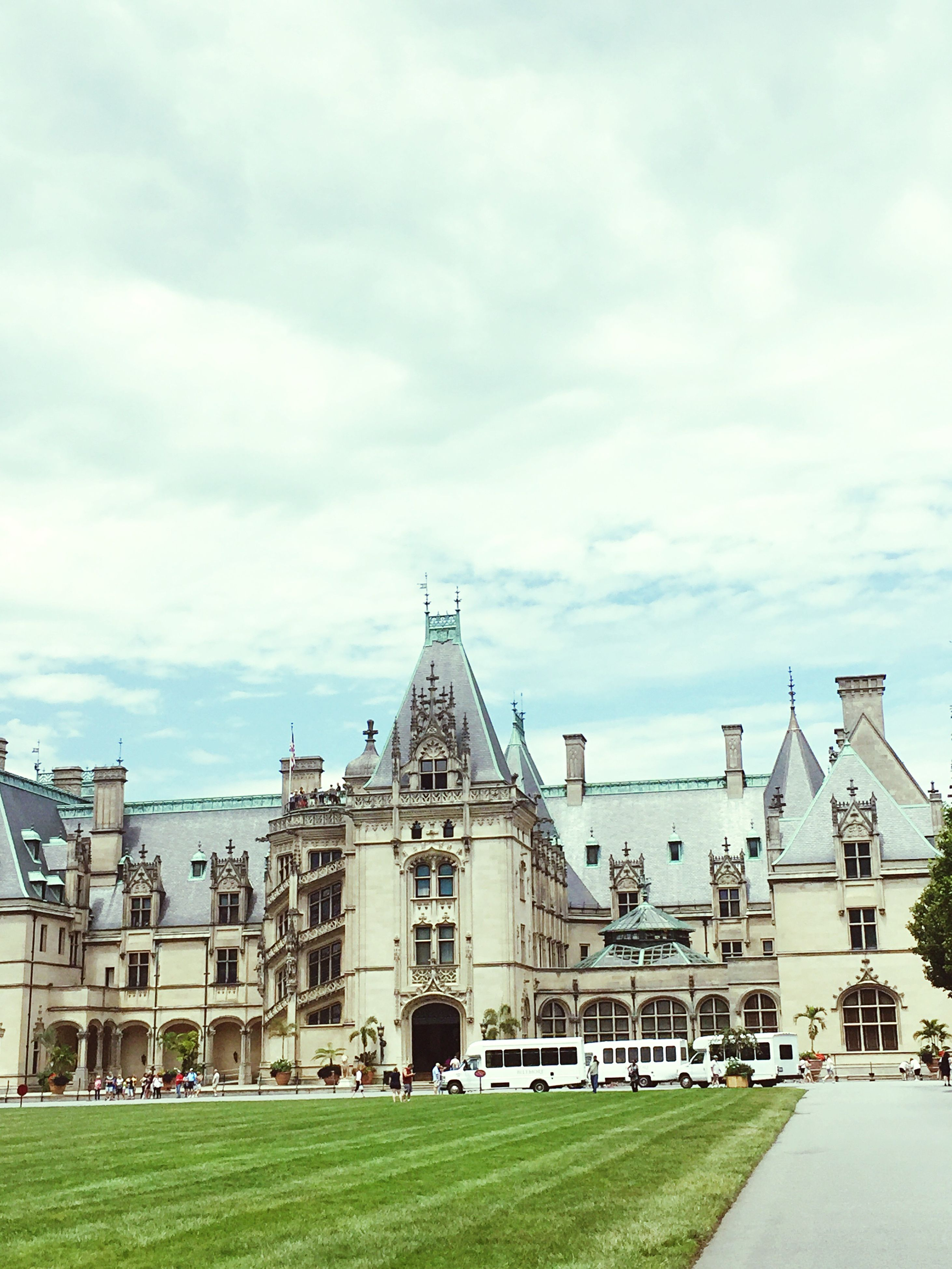 architecture, built structure, sky, grass, cloud - sky, cloudy, cloud, day, outdoors, lawn, green color, no people, facade, travel destinations, nature, exterior, grassy, overcast, blue