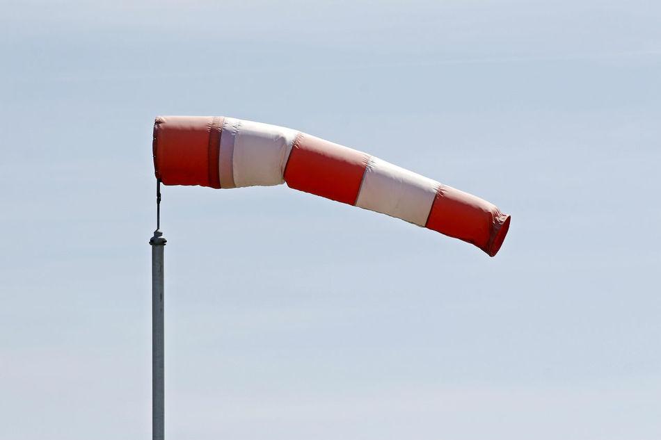 Anemometer in the wind Airfield Anemometer Blue Background Day Flying No People Outdoors Red Red White Sky Wind Wind Direction Indicator Wind Pants Windy