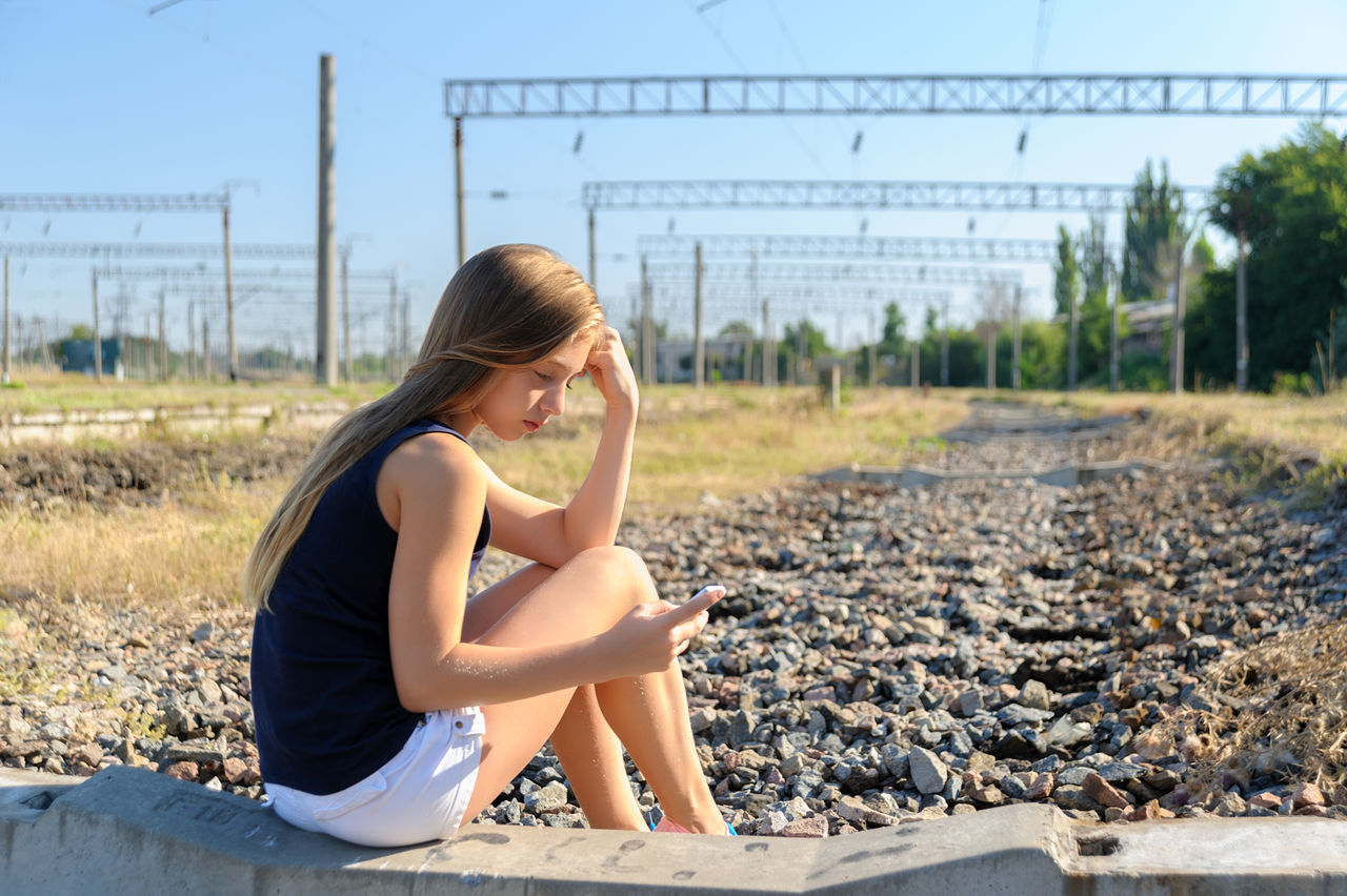 Girl teenager in top and shorts using cellphone while sitting on concrete of unfinished rail track in the countryside Caucasian Cellphone Day Girl Horizontal Mobile Nature One Person Outdoors Phone Rail Railway Sad Shorts Sit Smartphone Teen Teeneger Use Young Adult