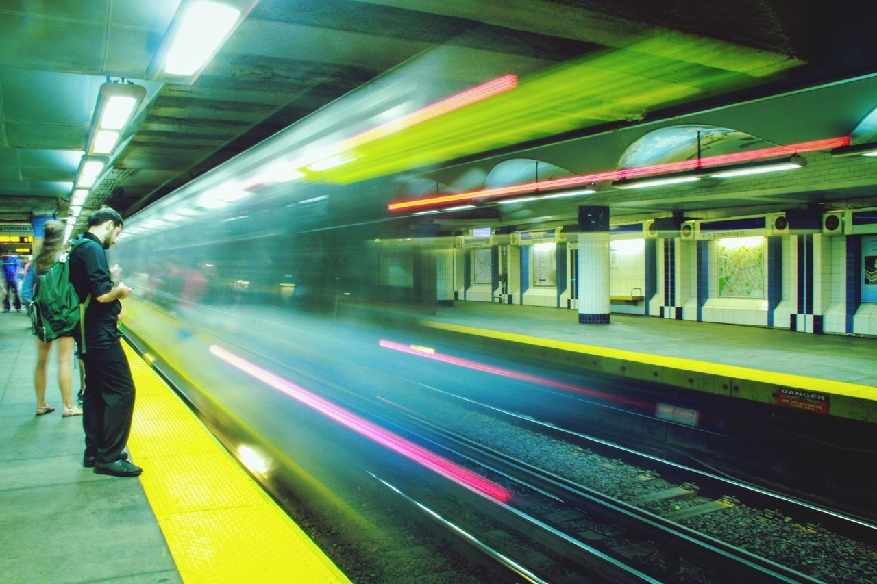 transportation, illuminated, public transportation, railroad station platform, railroad station, rail transportation, train - vehicle, blurred motion, speed, night, railroad track, mode of transport, motion, real people, men, full length, indoors, one person, subway train, people
