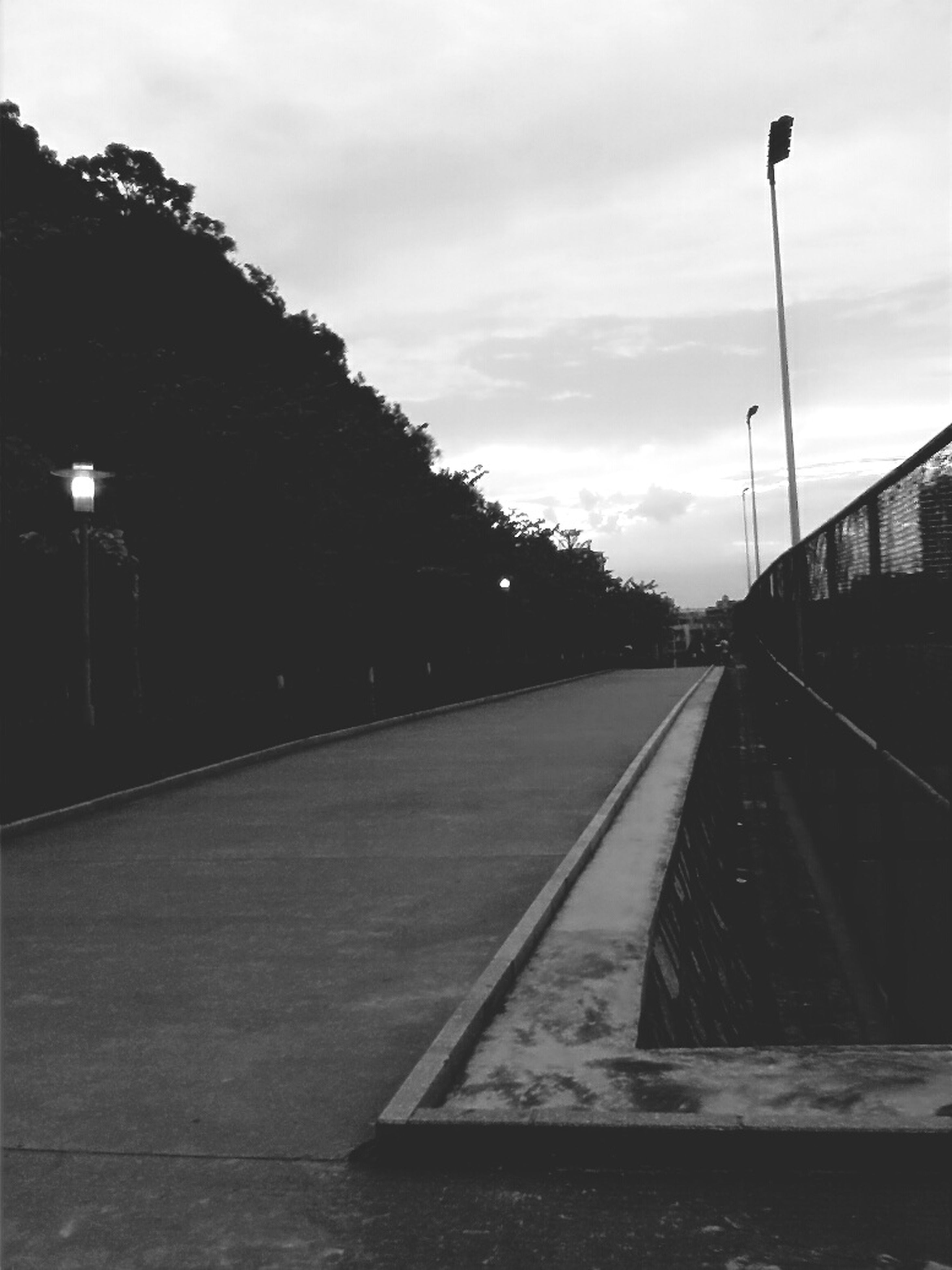 the way forward, sky, transportation, diminishing perspective, vanishing point, cloud - sky, road, railroad track, road marking, street light, tree, cloudy, empty, surface level, cloud, long, street, built structure, dusk, outdoors