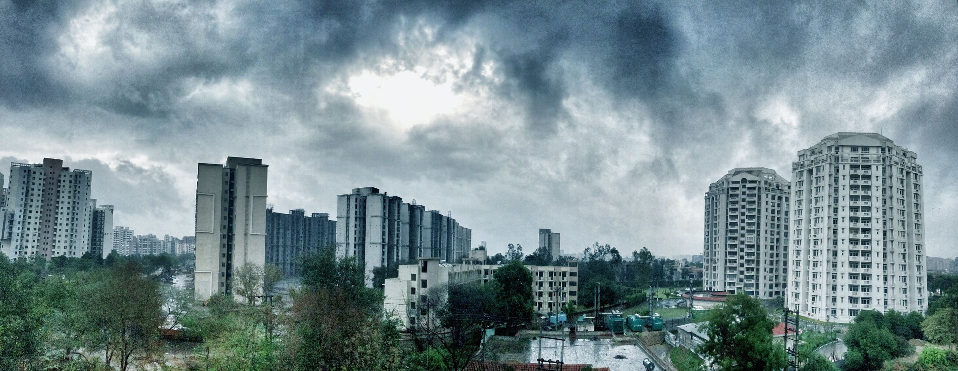 building exterior, architecture, built structure, city, sky, cloud - sky, skyscraper, tree, cloudy, cityscape, modern, tall - high, office building, cloud, tower, urban skyline, growth, building, city life, residential building
