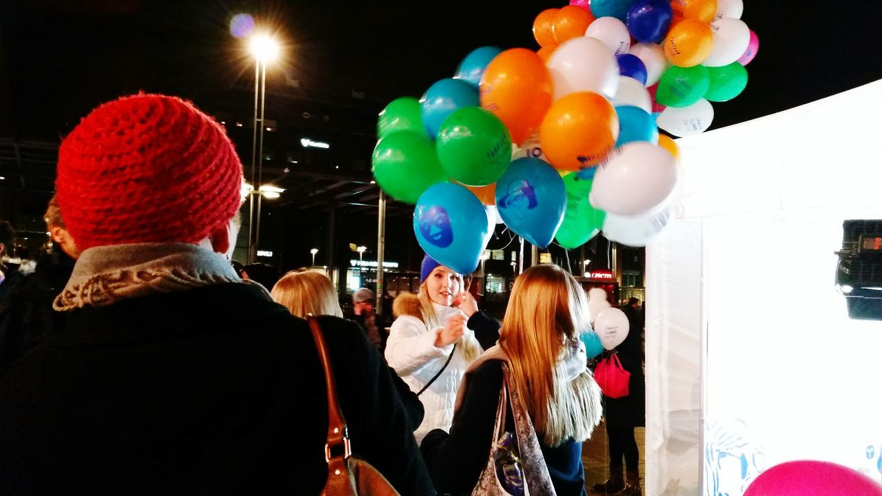 balloon, celebration, real people, multi colored, women, helium balloon, lifestyles, men, togetherness, fun, leisure activity, enjoyment, happiness, large group of people, friendship, outdoors, young women, night, warm clothing, crowd, young adult, people