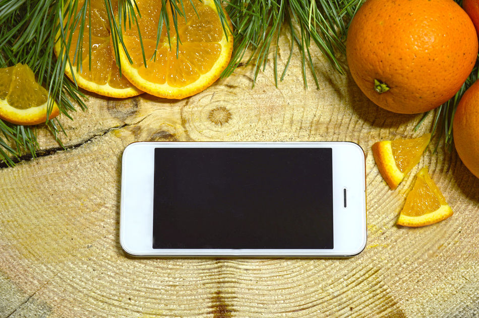 Phone closeup lying on the orange background Backdrop Branches Call Cellphone Colorful Communication Connection Design Digital Display Electronics  Gadget Juice Keyboard Modern Network Orange Portable Press Screen Technology Wood - Material