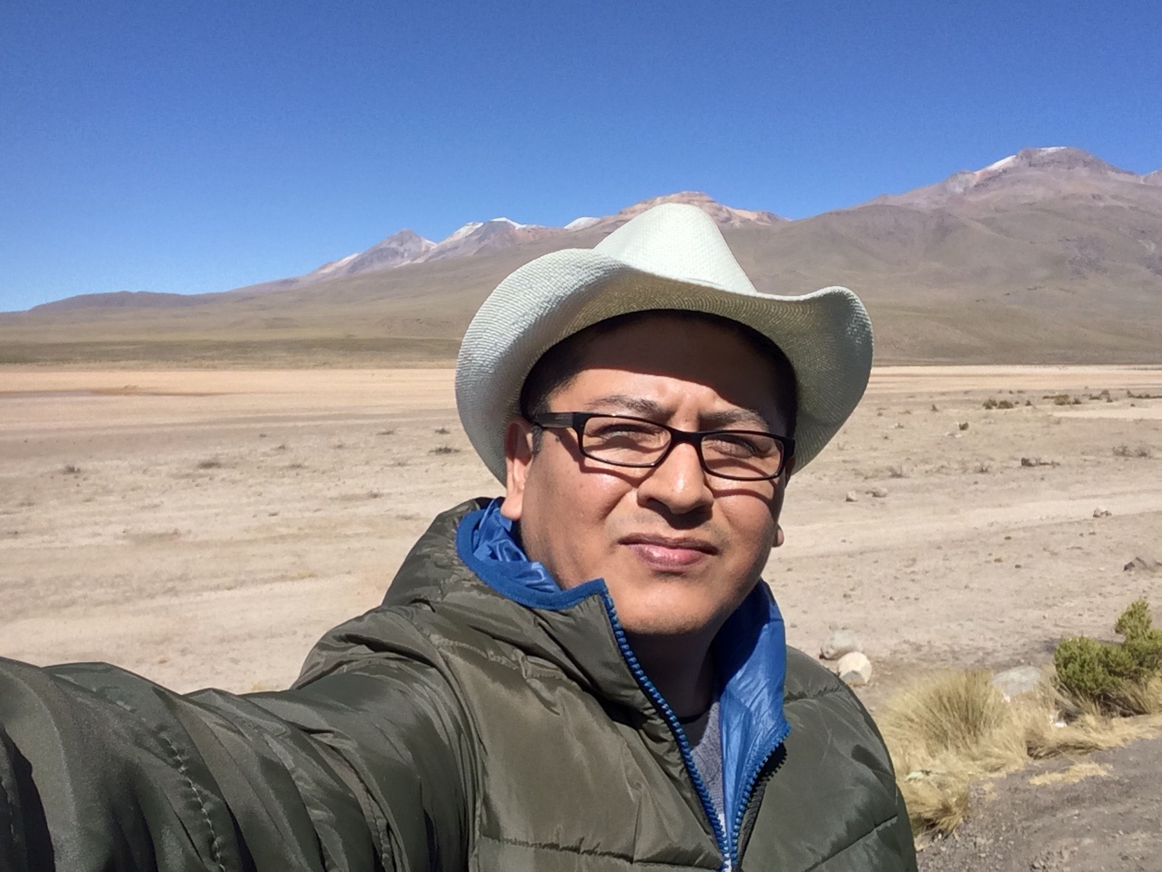 clear sky, leisure activity, headshot, lifestyles, looking at camera, mountain, exploration, adventure, casual clothing, blue, hiker, tourist, hiking, scenics, vacations, non-urban scene, person, nature, outdoors, tourism, beauty in nature, sunny, tranquil scene