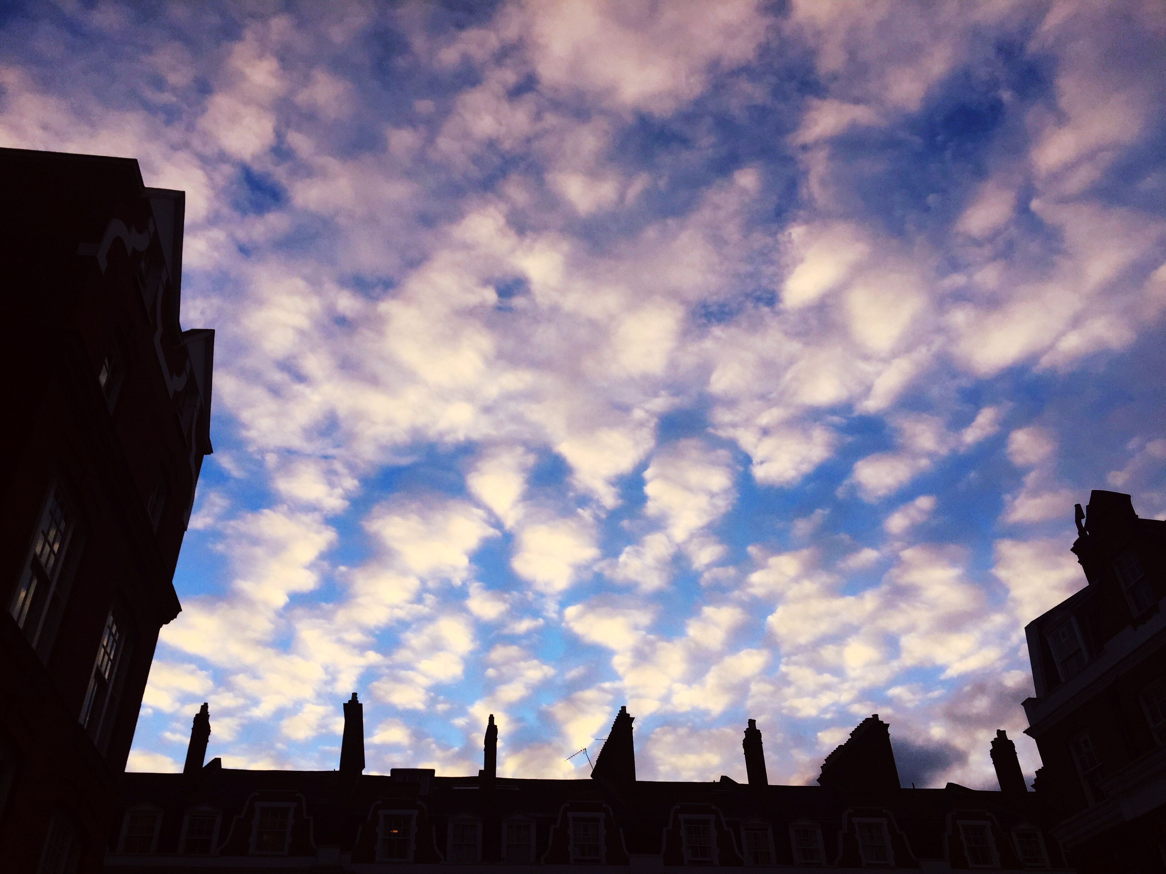 architecture, building exterior, sky, low angle view, built structure, cloud - sky, cloudy, cloud, building, city, silhouette, outdoors, high section, sunset, overcast, residential building, no people, weather, residential structure, dusk