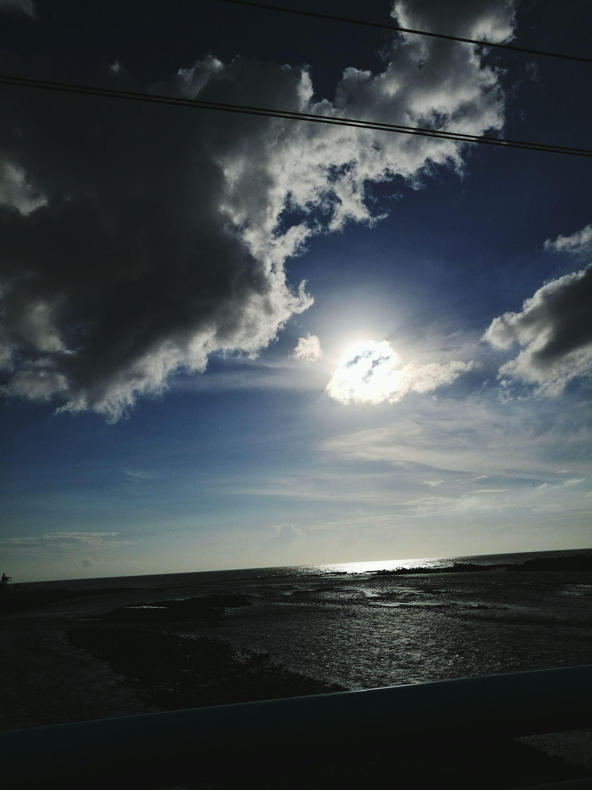 sea, water, tranquil scene, scenics, horizon over water, tranquility, beach, sky, beauty in nature, shore, calm, idyllic, nature, cloud - sky, coastline, cloud, ocean, sun, non-urban scene, tourism, outdoors, blue, vacations, seascape, remote, no people, majestic, cloudy, cloudscape
