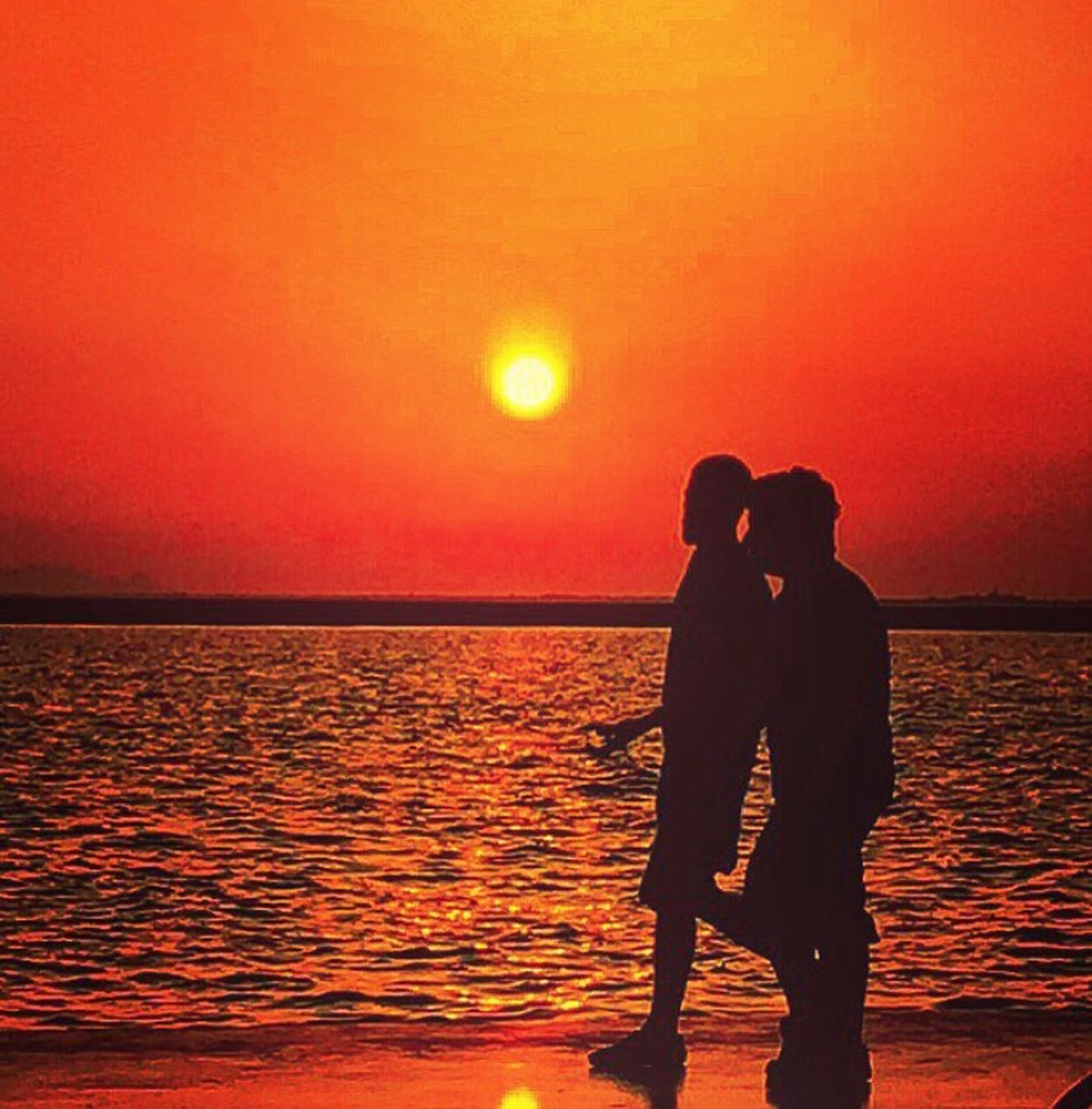 sunset, orange color, water, silhouette, sea, sun, standing, leisure activity, lifestyles, horizon over water, scenics, beauty in nature, tranquil scene, men, idyllic, tranquility, sky, nature