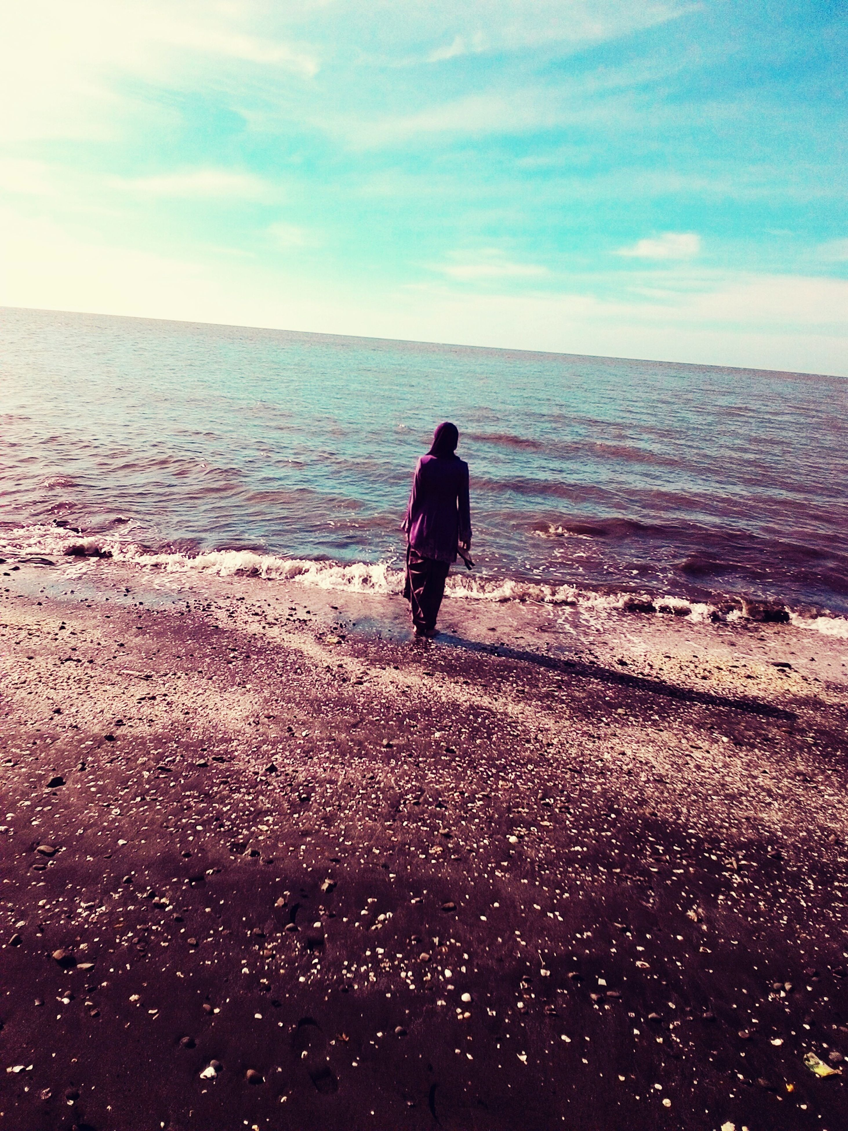 water, sea, horizon over water, full length, sky, rear view, beach, lifestyles, tranquil scene, standing, leisure activity, tranquility, silhouette, scenics, shore, beauty in nature, nature, getting away from it all