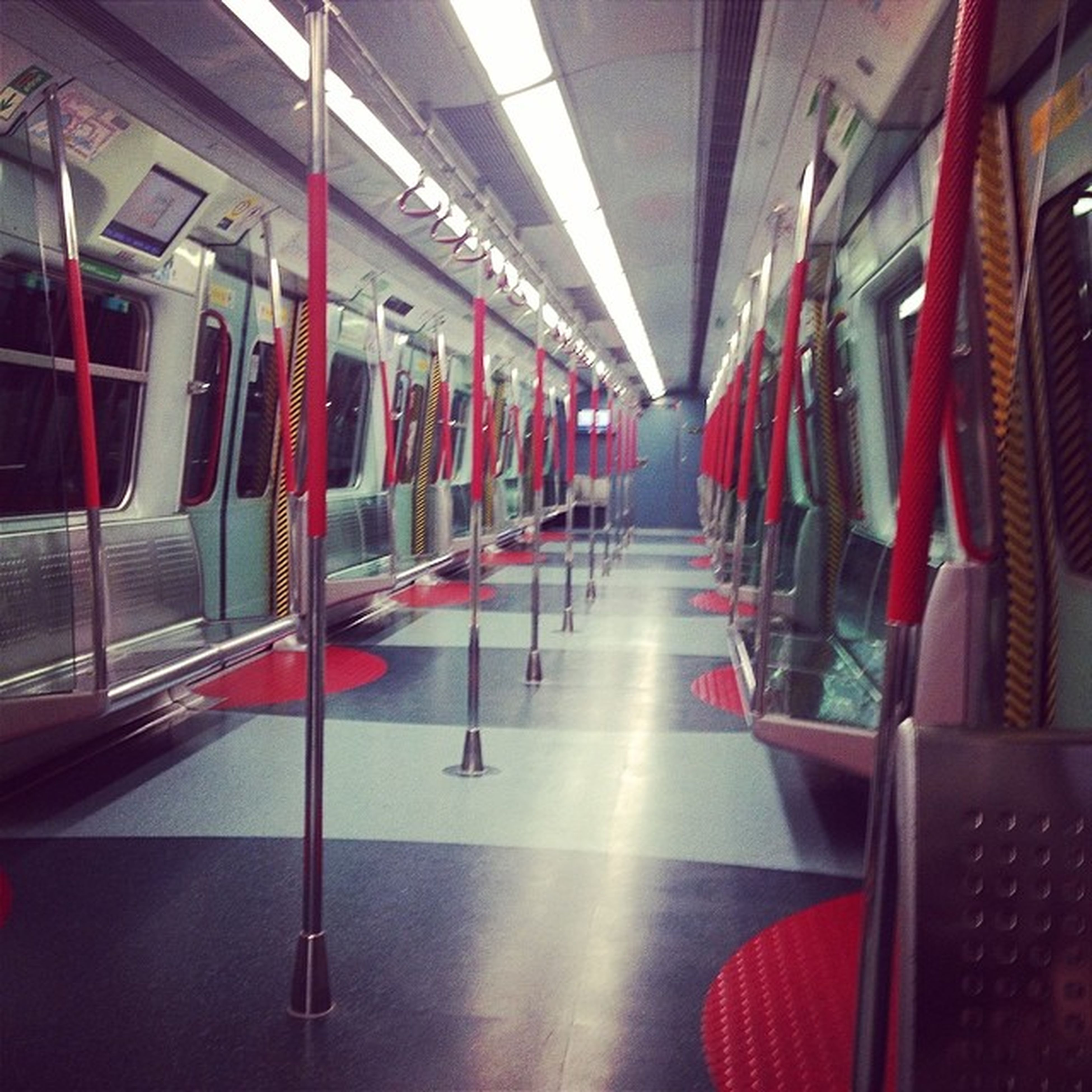 indoors, ceiling, absence, empty, modern, in a row, escalator, red, seat, transportation, architecture, chair, built structure, reflection, incidental people, flooring, tiled floor, glass - material, interior, vehicle seat
