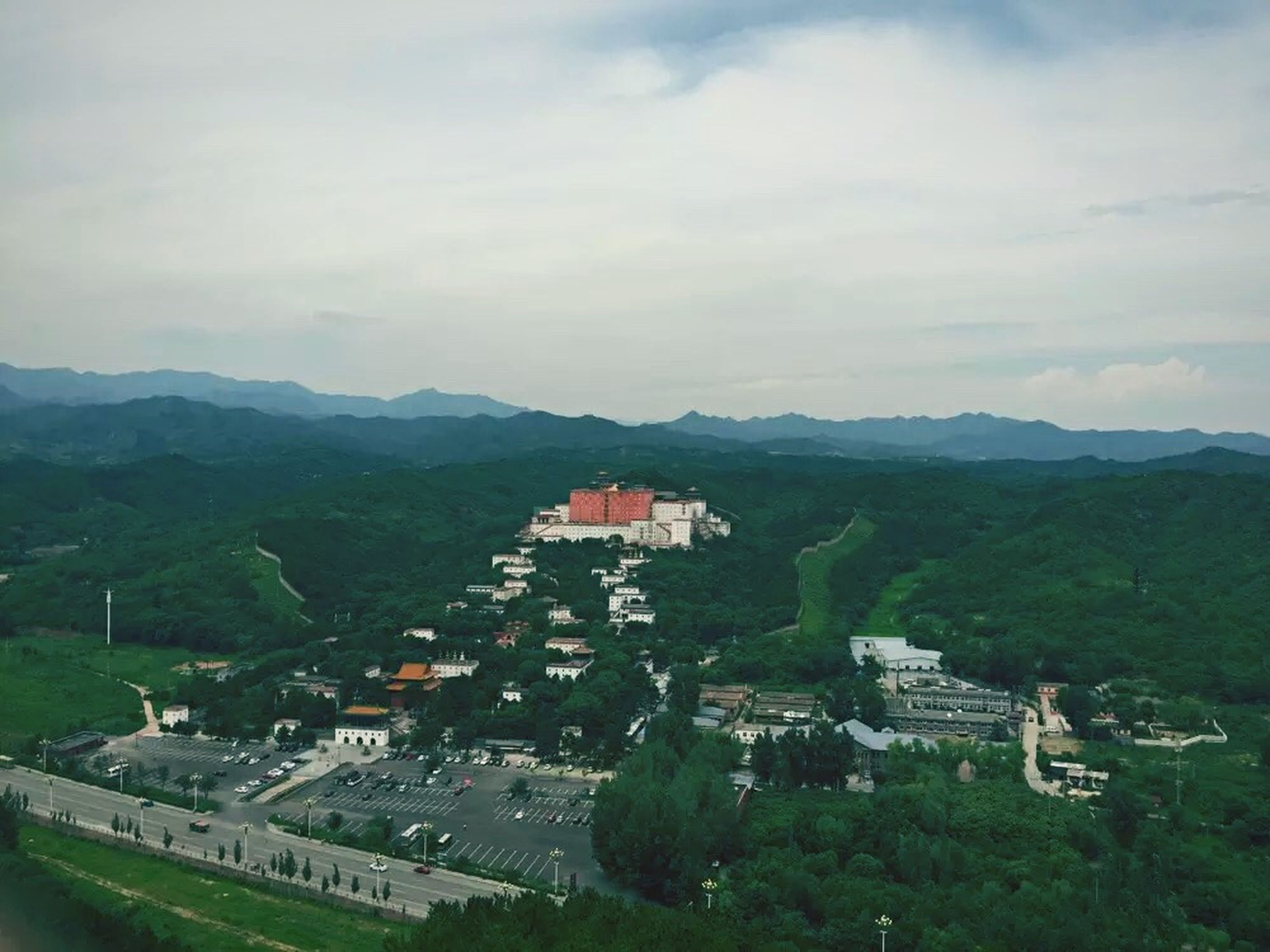 architecture, mountain, built structure, building exterior, house, sky, mountain range, high angle view, tree, landscape, residential structure, cloud - sky, town, hill, residential building, townscape, green color, scenics, cloud, day