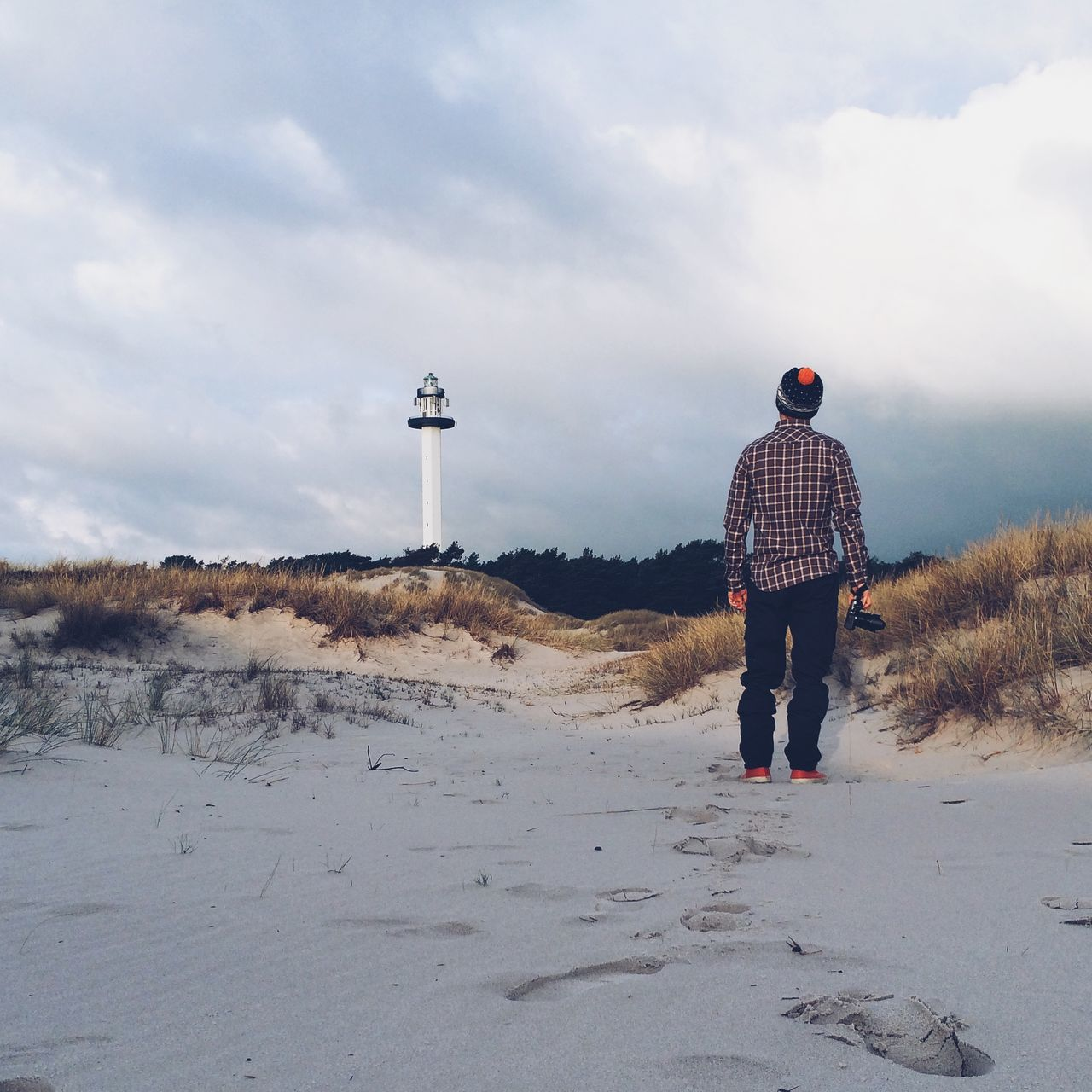 Rear View Of Man Looking At Lighthouse At Beach