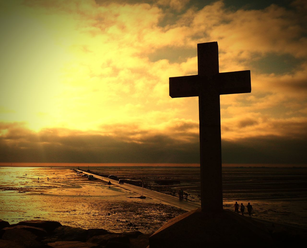 Low Angle View Of Silhouette Cross By Sea Against Cloudy Sky During Sunset