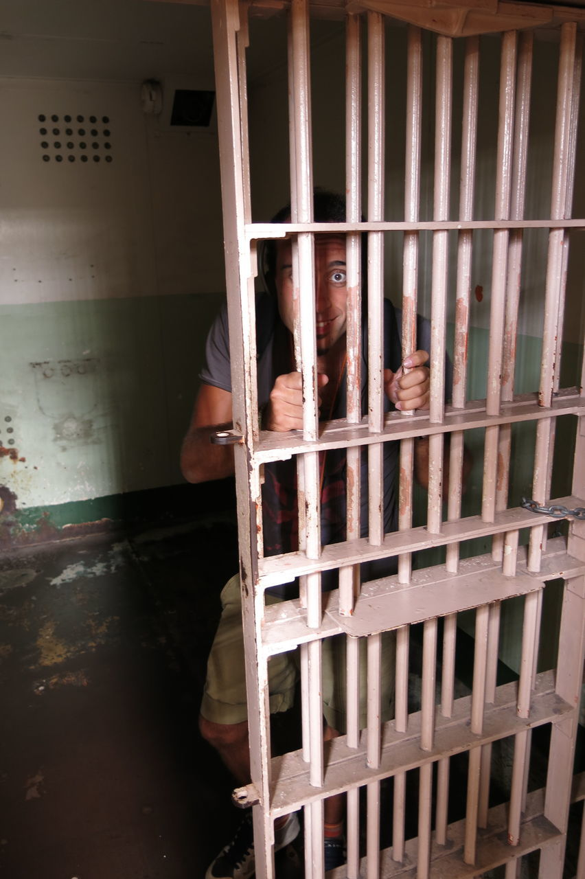 prison bars, prison, prison cell, punishment, indoors, prisoner, trapped, security bar, crime, justice - concept, looking at camera, real people, men, cage, confined space, law, one person, close-up, day, people