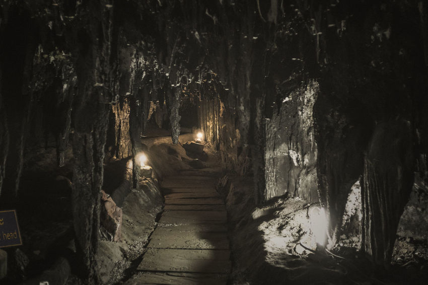 In the Dark Cave. Bulb Cave Dark Darkness And Light Diminishing Perspective Illuminated Lamp Lifestyles Light Narrow Nature Outdoors Rock Shadow Stalactite  Stalagmite The Way Forward Vanishing Point