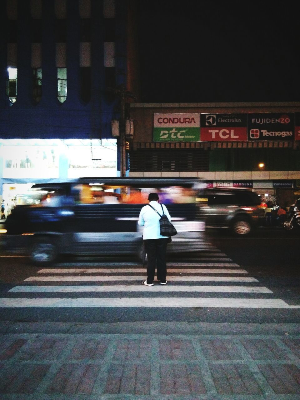 transportation, blurred motion, text, illuminated, architecture, real people, men, street, city, one person, city life, built structure, building exterior, road, night, full length, land vehicle, communication, car, walking, rear view, outdoors, motion, standing, lifestyles, one man only, adult, people